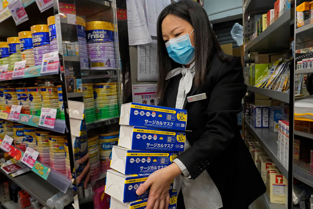 An employee carries boxes of face masks as people queue up to buy face masks at a cosmetics shop in Hong Kong, Thursday, January, 30. The masks in the photo were not part of the seizure.