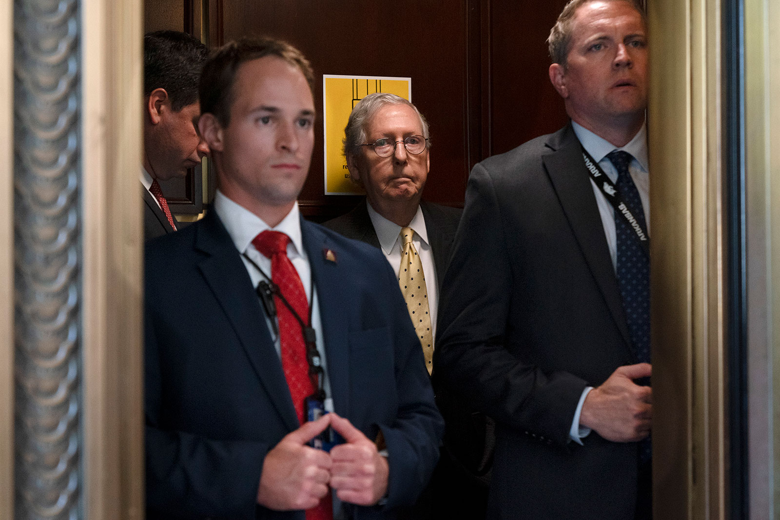 Senate Minority Leader Mitch McConnell, center, rides in an elevator after a meeting on Capitol Hill on Tuesday, May 18.