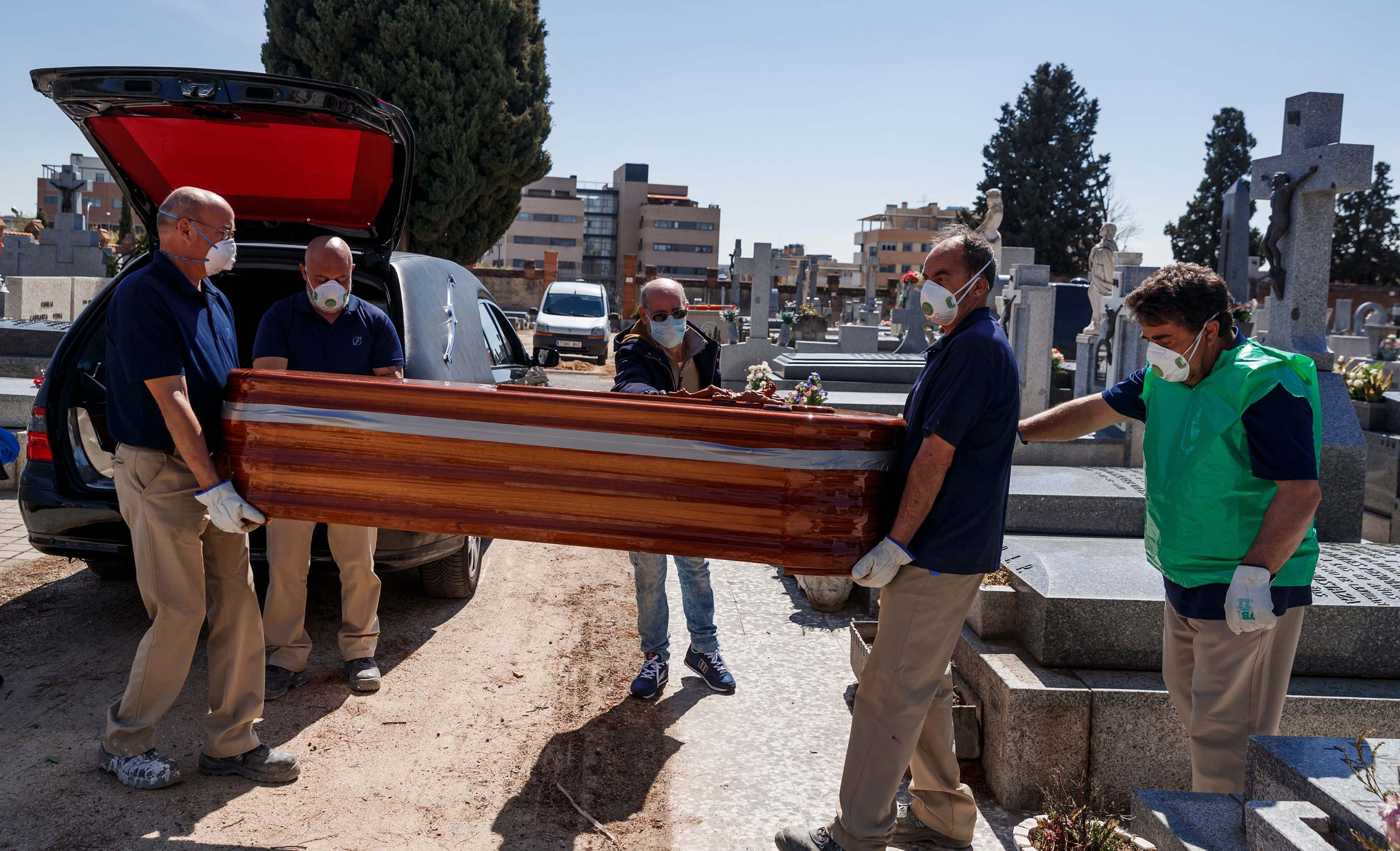 Mortuary employees carry the coffin of a coronavirus victim during a burial at the Fuencarral cemetery in Madrid, on March 29.