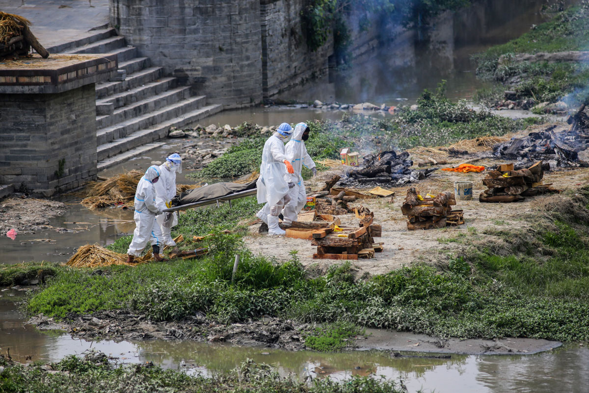 Men wearing personal protective equipment carry the body of a Covid-19 victim to cremate on the bank of Bagmati River in Kathmandu, Nepal on May 3.