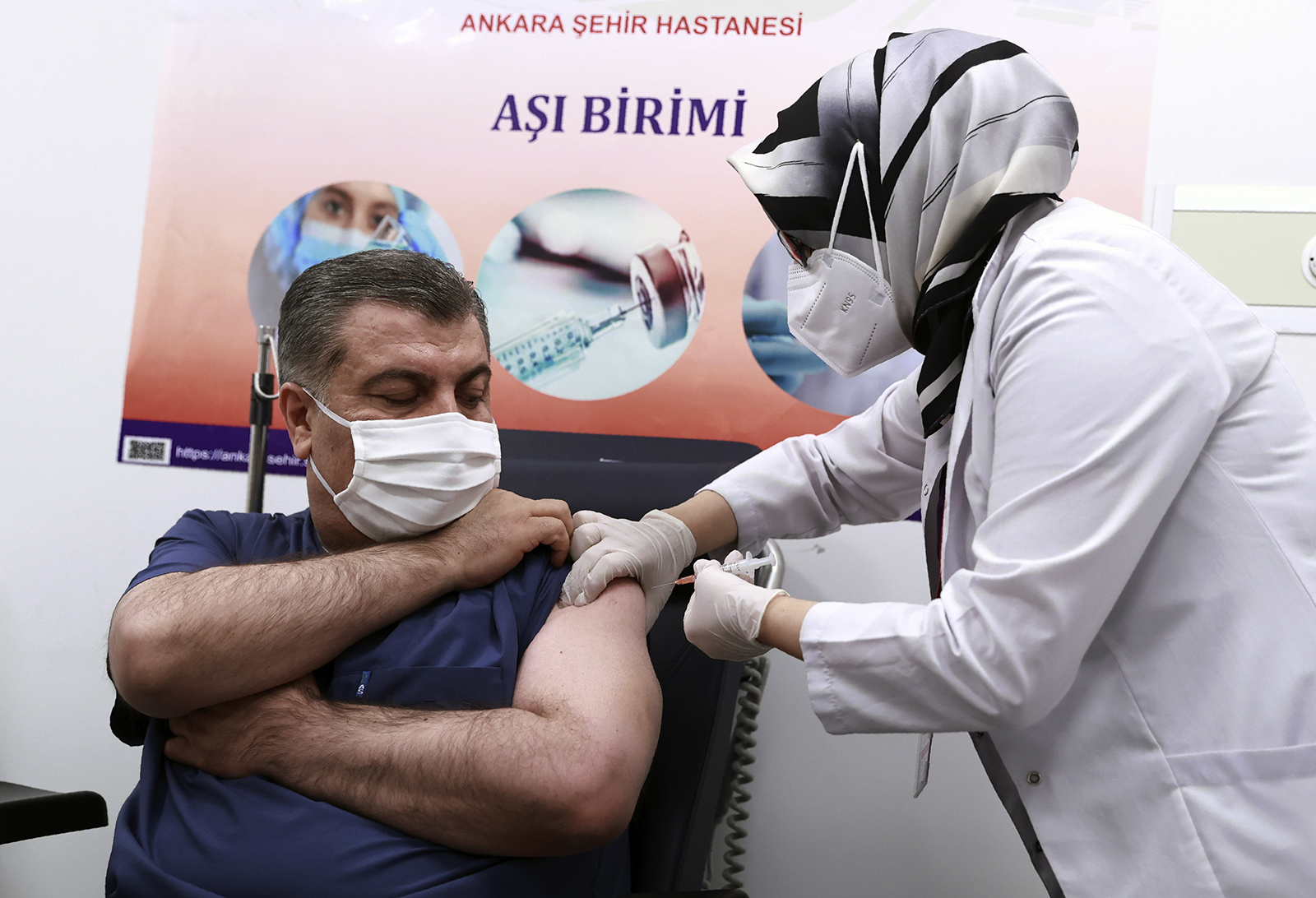 Turkey's Health Minister Fahrettin Koca receives the first shot after Turkish authorities gave the go-ahead for the emergency use of the Covid-19 vaccine produced by China's Sinovac Biotech, in Ankara, Turkey, on Wednesday, January 13.