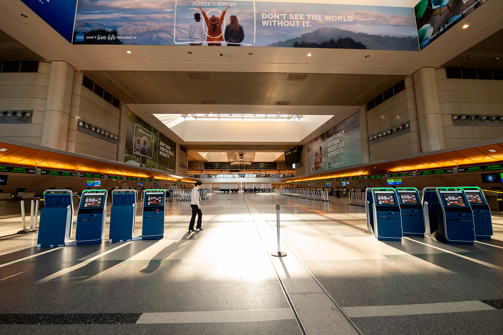 A woman walks through an empty Tom Bradley Terminal at Los Angeles International Airport on April 16, in Los Angeles.