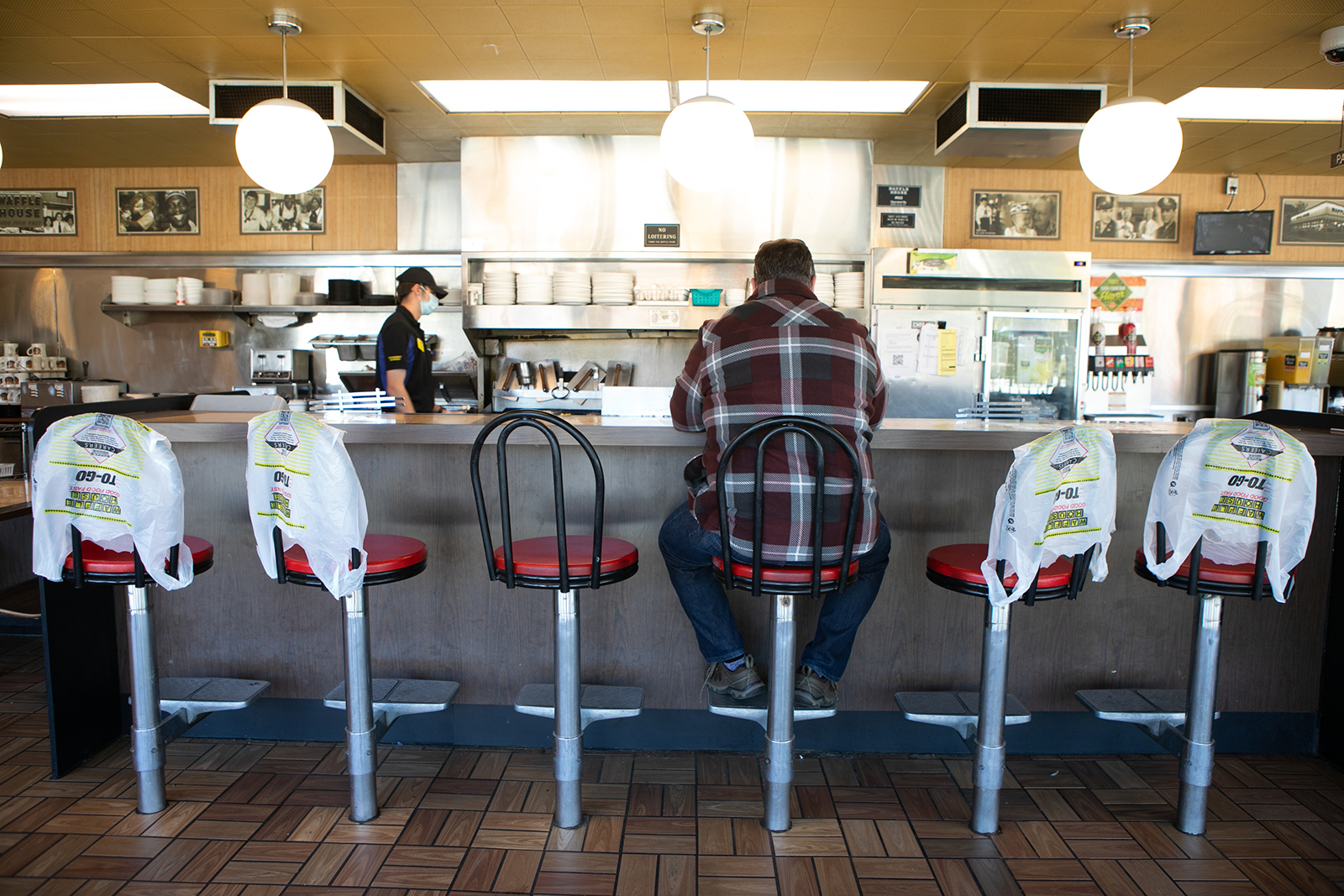 Ron Flexon sits at the counter for dine-in service while other seats are marked off for social distancing protocol at Waffle House on April 27, in Brookhaven, Georgia.