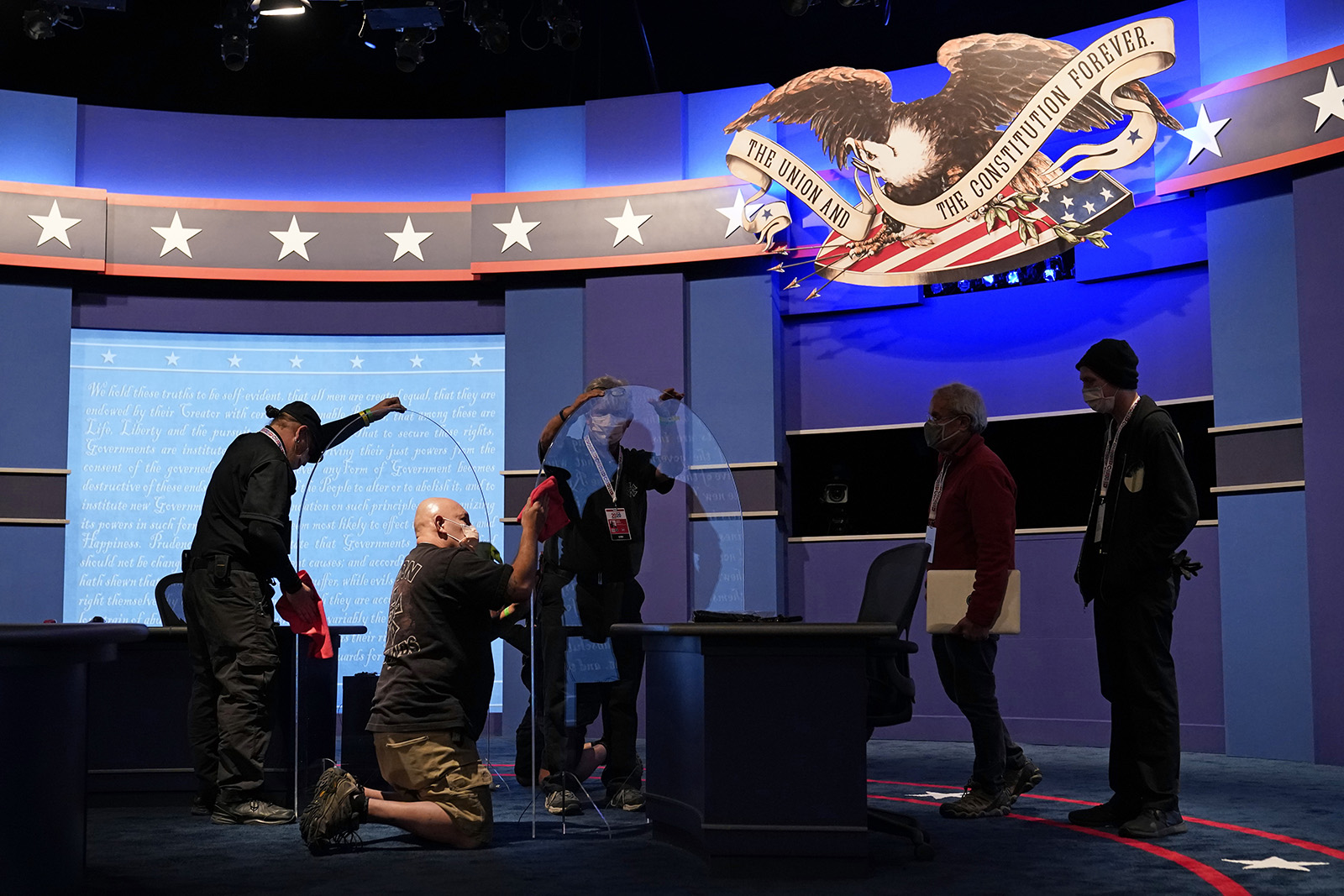 Workers clean protective plastic panels onstage between tables for Vice President Mike Pence and Democratic vice presidential candidate, Sen. Kamala Harris, as preparations take place for the vice presidential debate at the University of Utah on Tuesday in Salt Lake City.