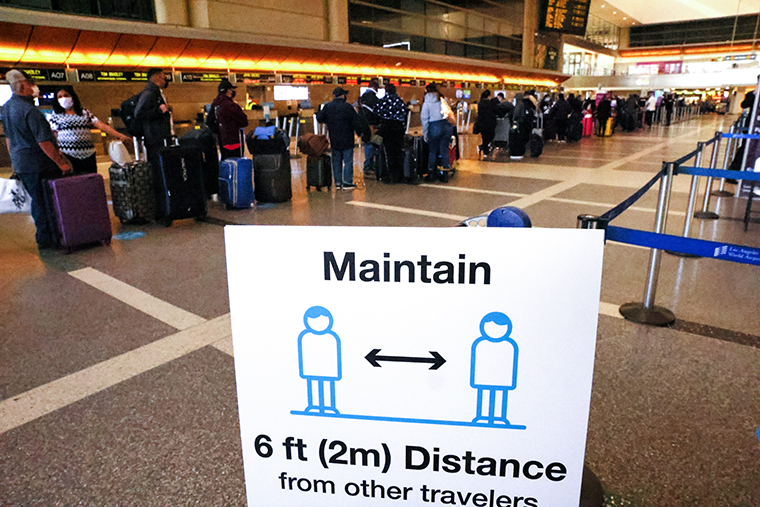 Travelers wait in line to check in for a flight at the Tom Bradley International Terminal at Los Angeles International Airport (LAX) amid a COVID-19 surge in Southern California on December 22, 2020 in Los Angeles, California.