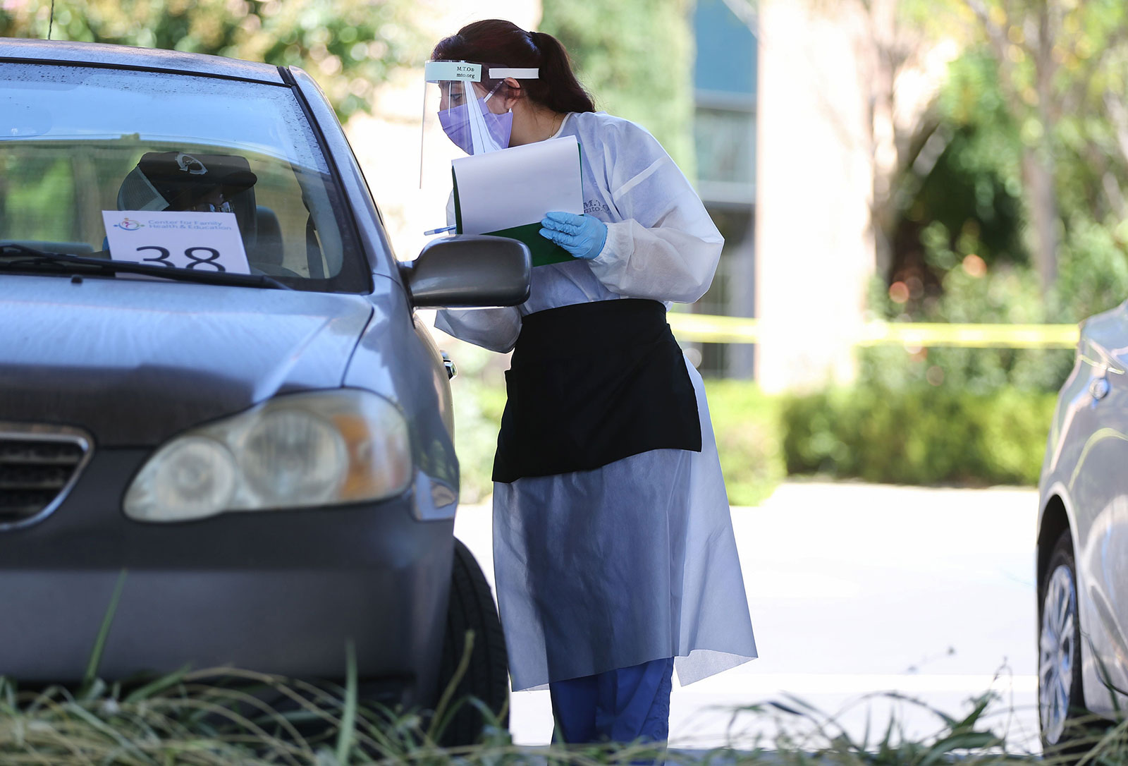 A healthcare worker gathers information from a person at a drive-in coronavirus testing center in Los Angeles on August 11.
