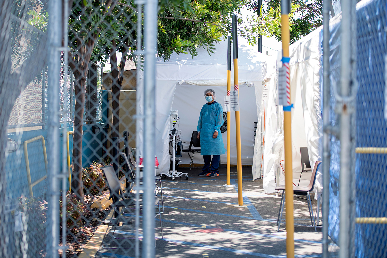 A health worker stands in a tent at a Covid-19 testing site at St. John's Well Child and Family Center, amid the novel coronavirus pandemic, July 24, in Los Angeles.