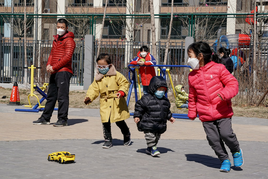 Children play in a garden in Beijing, China, on Saturday, as travel and movement restrictions begin to lift.