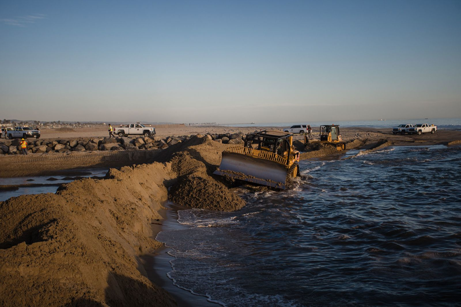 Excavators dredge sand to block some of the oil from flowing into Huntington Beach.
