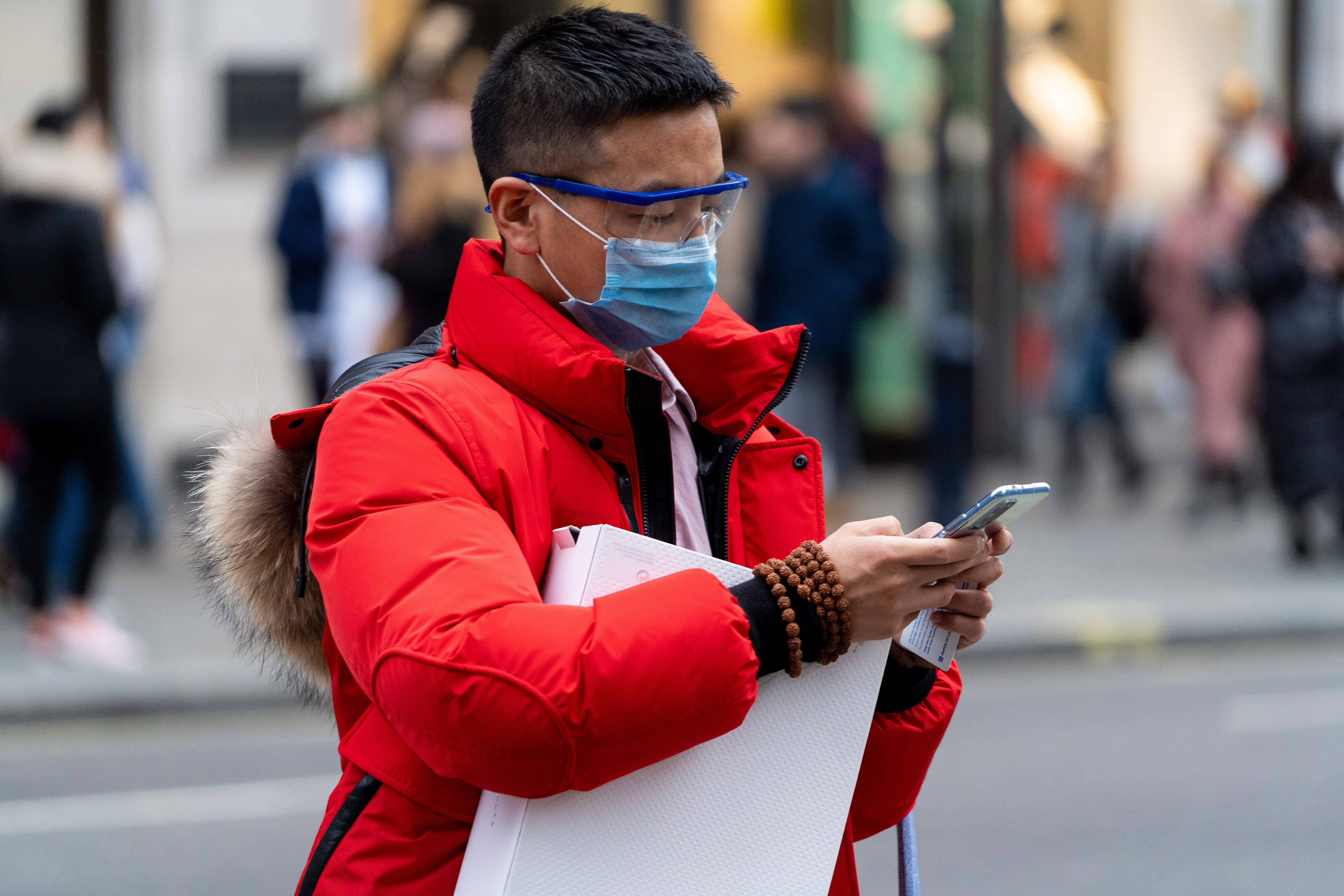A pedestrian wears a surgical mask as he checks his phone while walking along London's Regent Street in central London on Jan. 25. European airports from London to Moscow stepped up checks Wednesday on flights from the Chinese city at the heart of the coronavirus that has killed 41 people and spread to the United States.