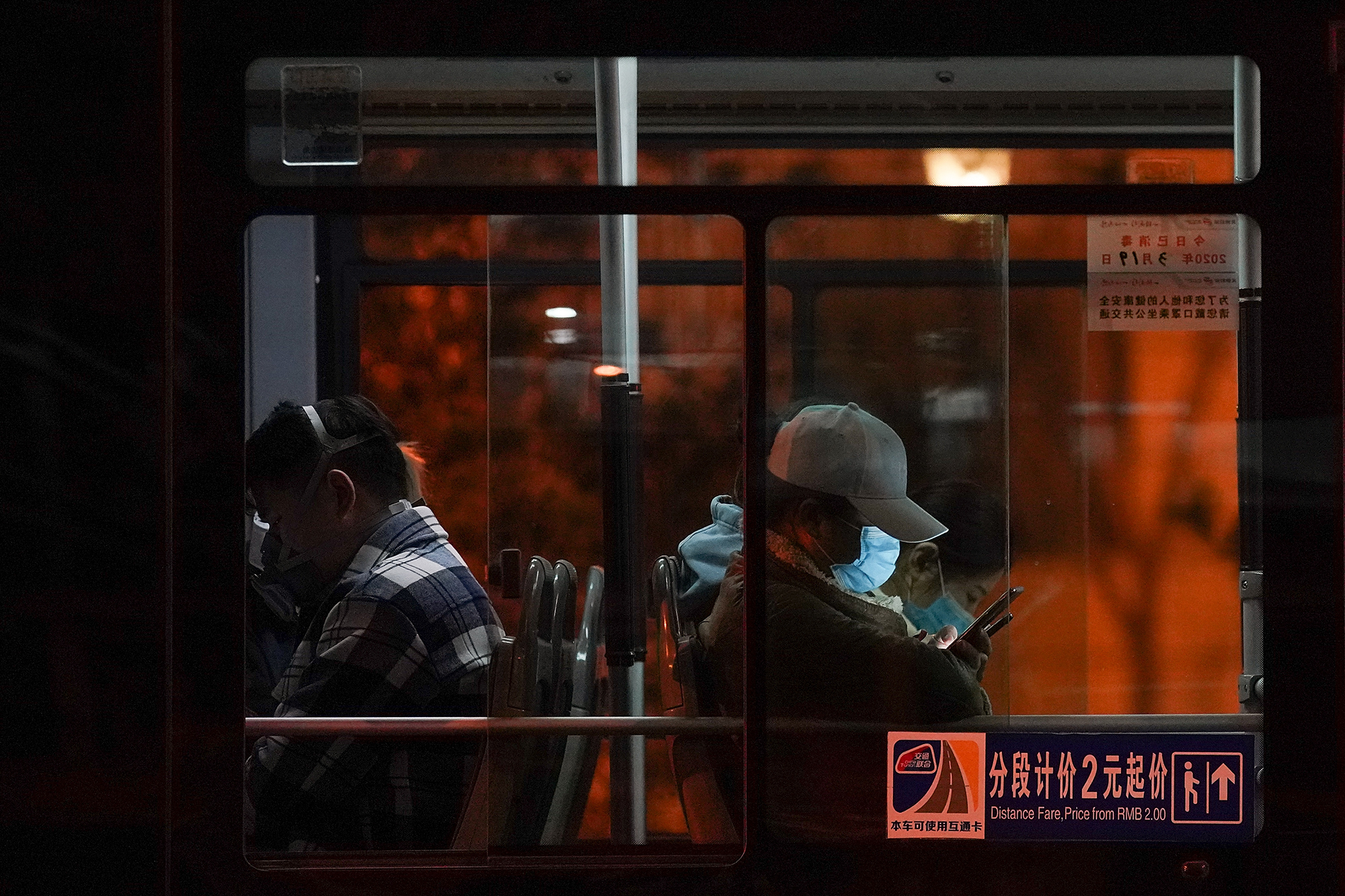 A Chinese man wears a protective mask as he rides the bus on March 19 in Beijing, China.