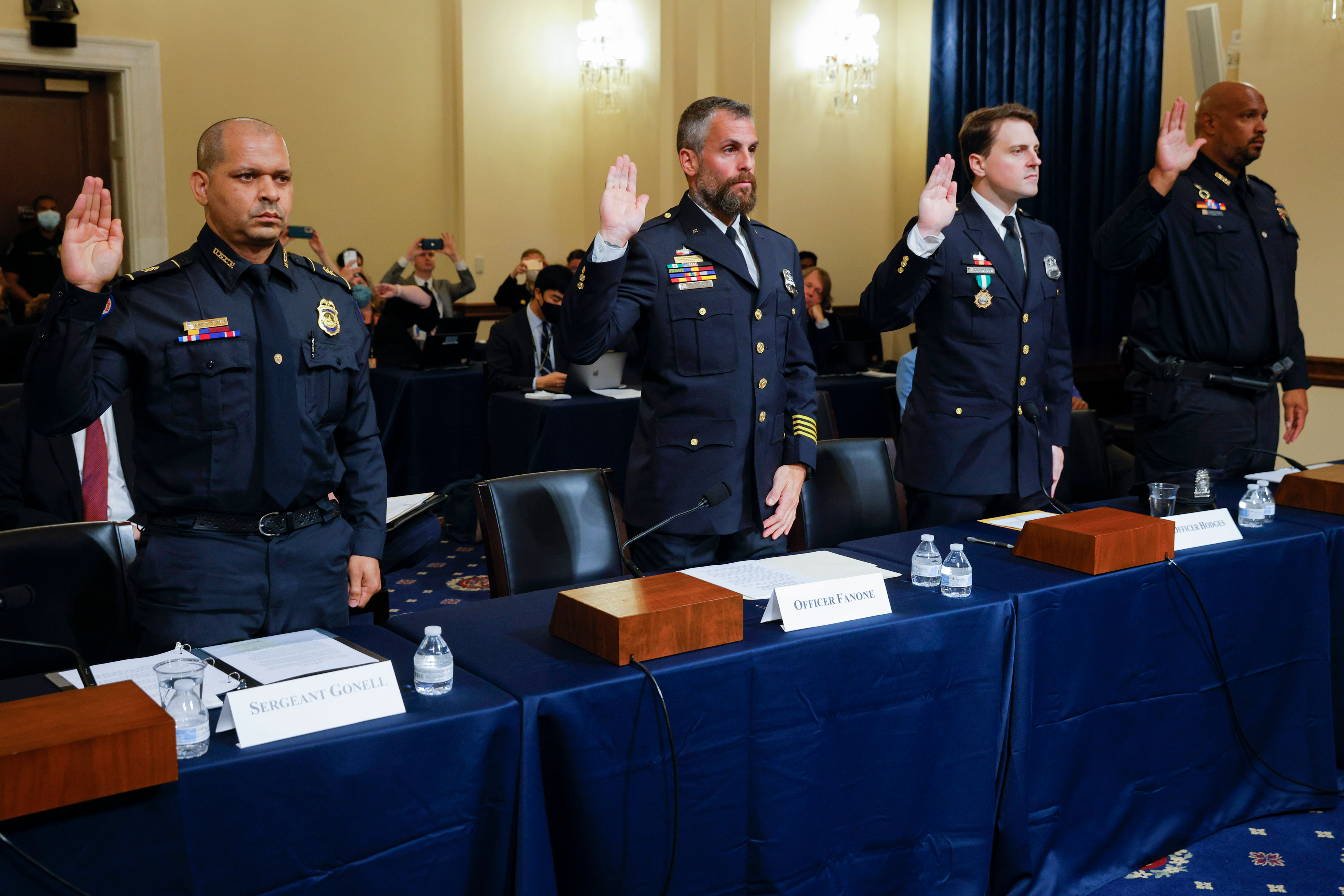 From left, US Capitol Police Sgt. Aquilino Gonell, DC police officer Michael Fanone, DC police officer Daniel Hodges, and US Capitol police officer Harry Dunn are sworn in to testify to the House select committee hearing on the January 6 attack on Capitol Hill on Tuesday, July 27.