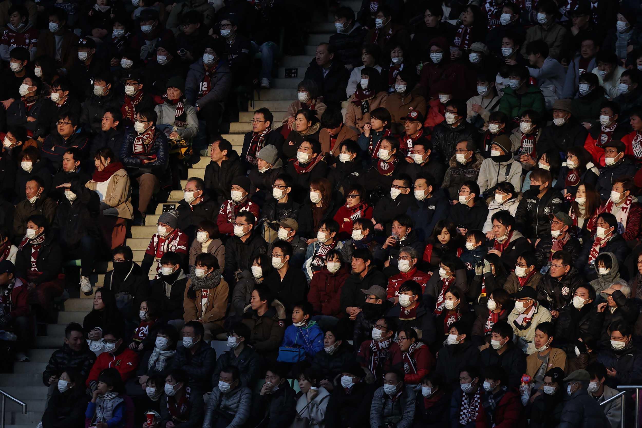 Spectators wearing face masks watch a J League soccer game in Kobe, Japan, on Sunday.