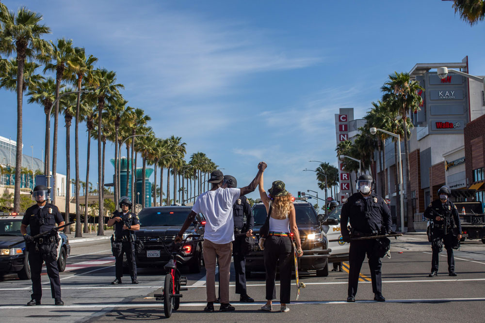 A black man and a white woman hold their hands up in a front of police officers in downtown Long Beach on May 31, 2020 during a protest against the death of George Floyd.