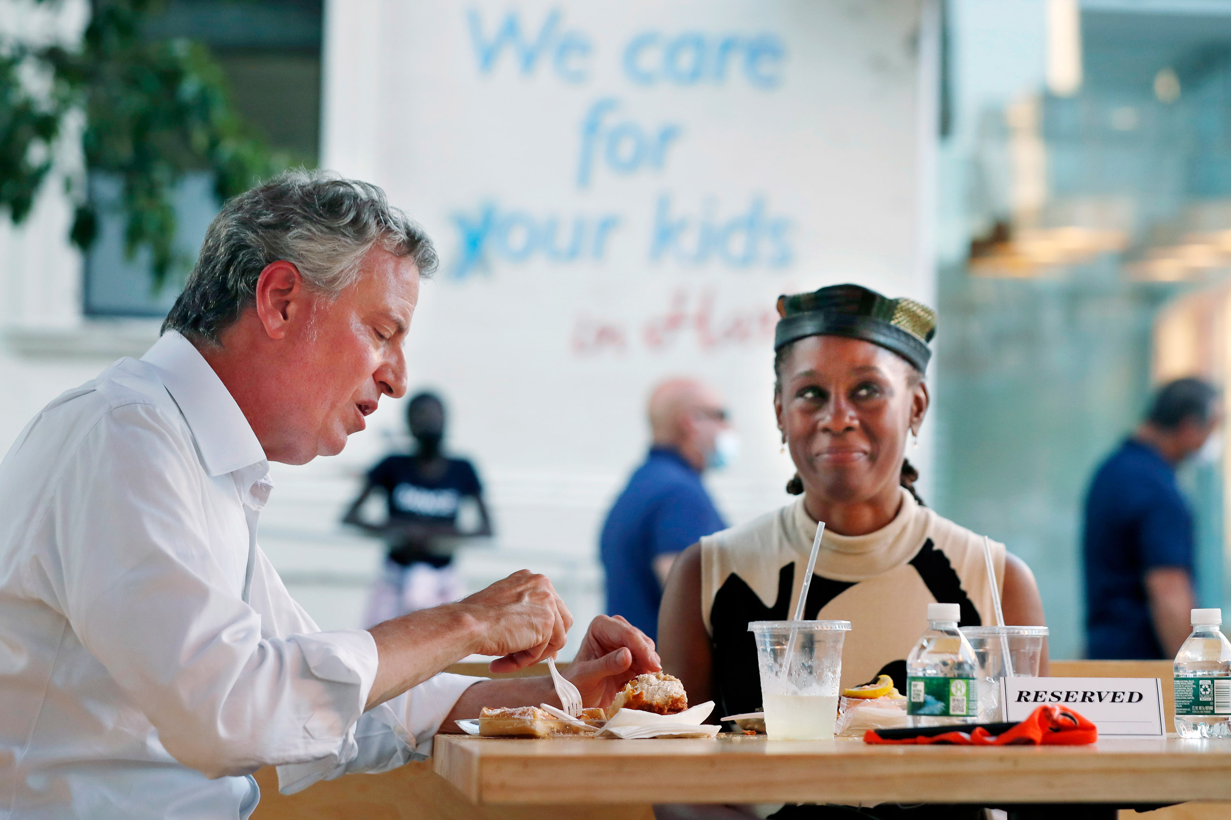 New York Mayor Bill de Blasio, left, dines with his wife Chirlane McCray in an outdoor booth at Melba's restaurant in Harlem on the first day of the Phase 2 reopening of the city during thecoronavirus pandemic Monday, June 22, 2020, in New York. (AP Photo/