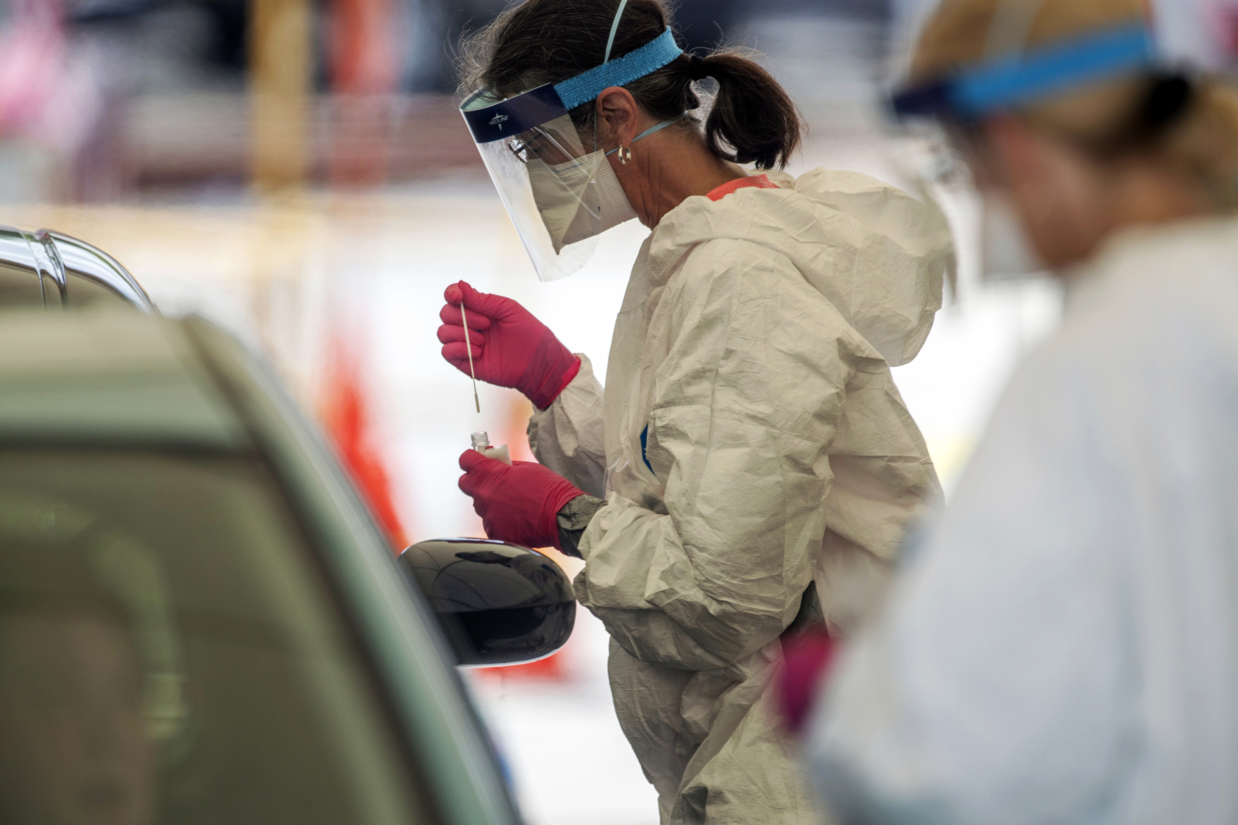 A medical healthcare worker takes samples for the coronavirus at a community testing site in the parking lot of La Flor de Jalisco #2 in Gainesville, Georgia, on May 15.
