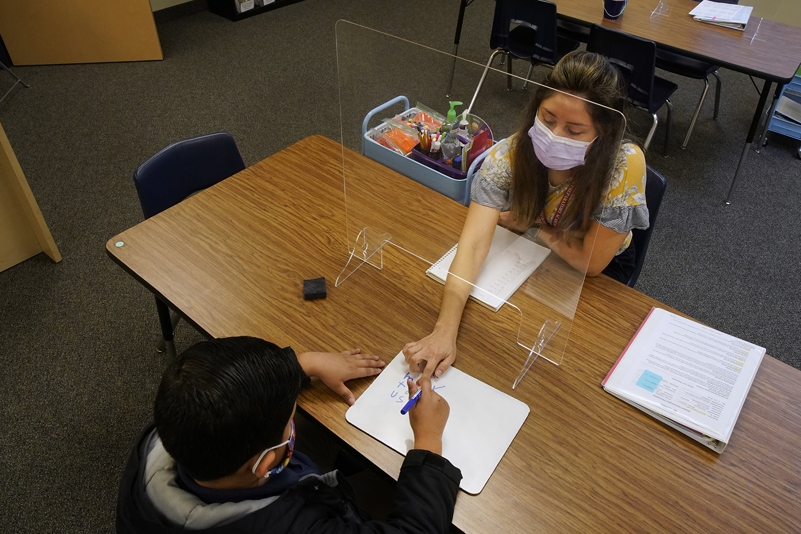 A teacher works with a student with a plexiglass shield dividing them at Freedom Preparatory Academy on February 10, in Provo, Utah.