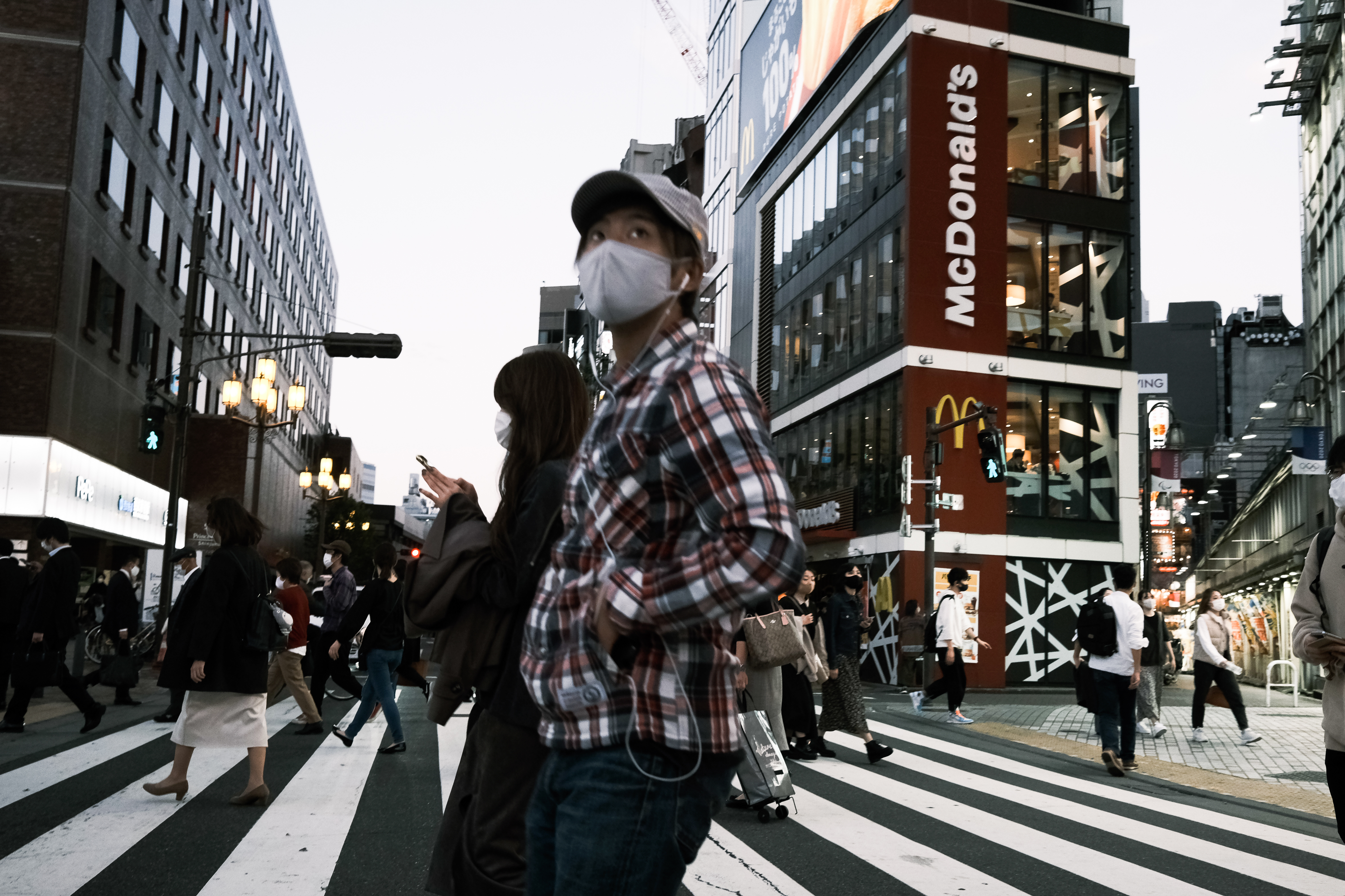 Pedestrians wearing protective masks in the Shinjuku district of Tokyo, Japan, on Thursday, Nov. 28.