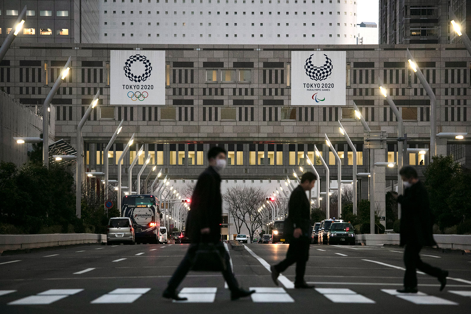 People walk across a pedestrian crossing near the Tokyo Metropolitan Government building in Tokyo on March 3.