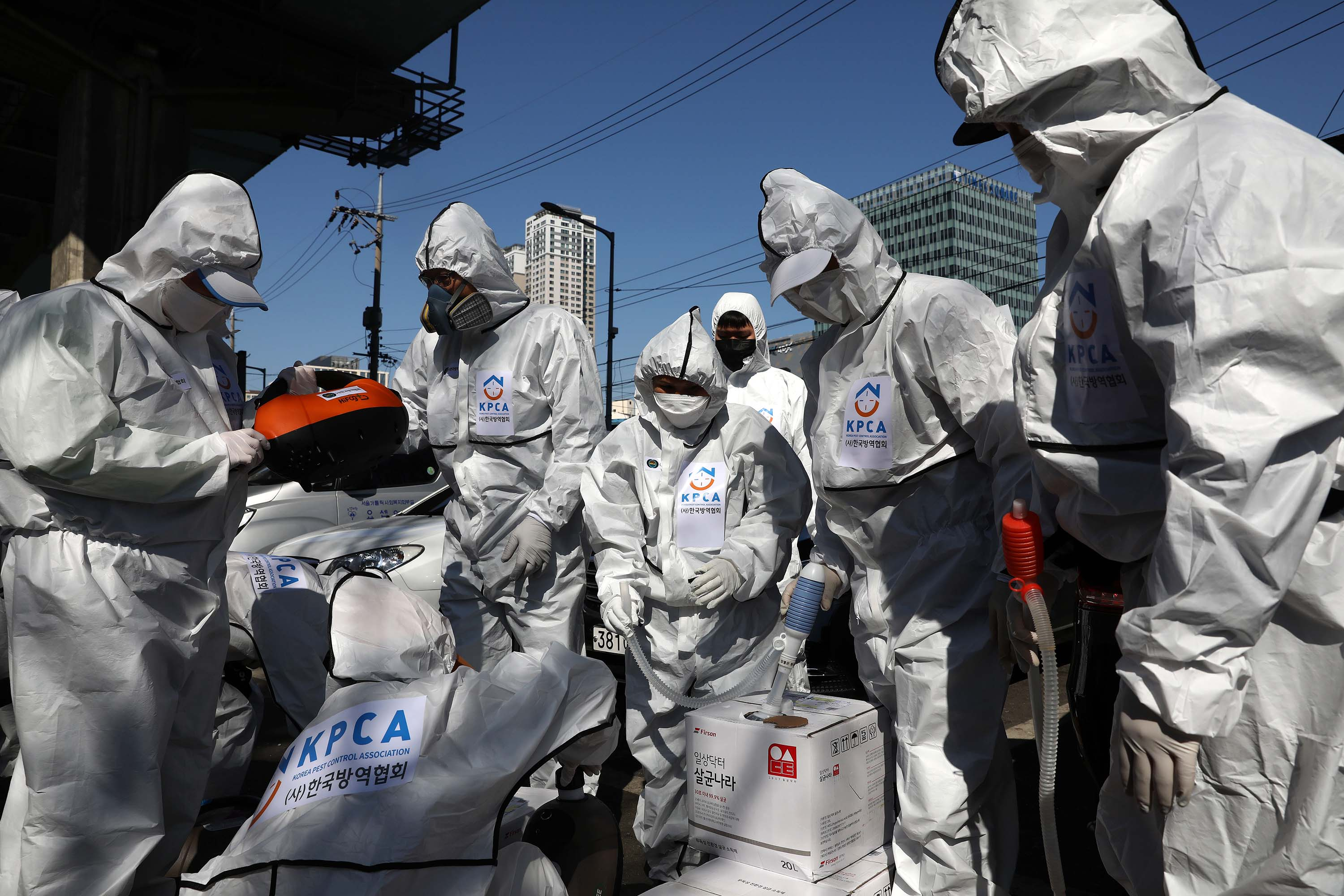 Workers prepare to disinfect a neighborhood in Seoul, South Korea, on Sunday.