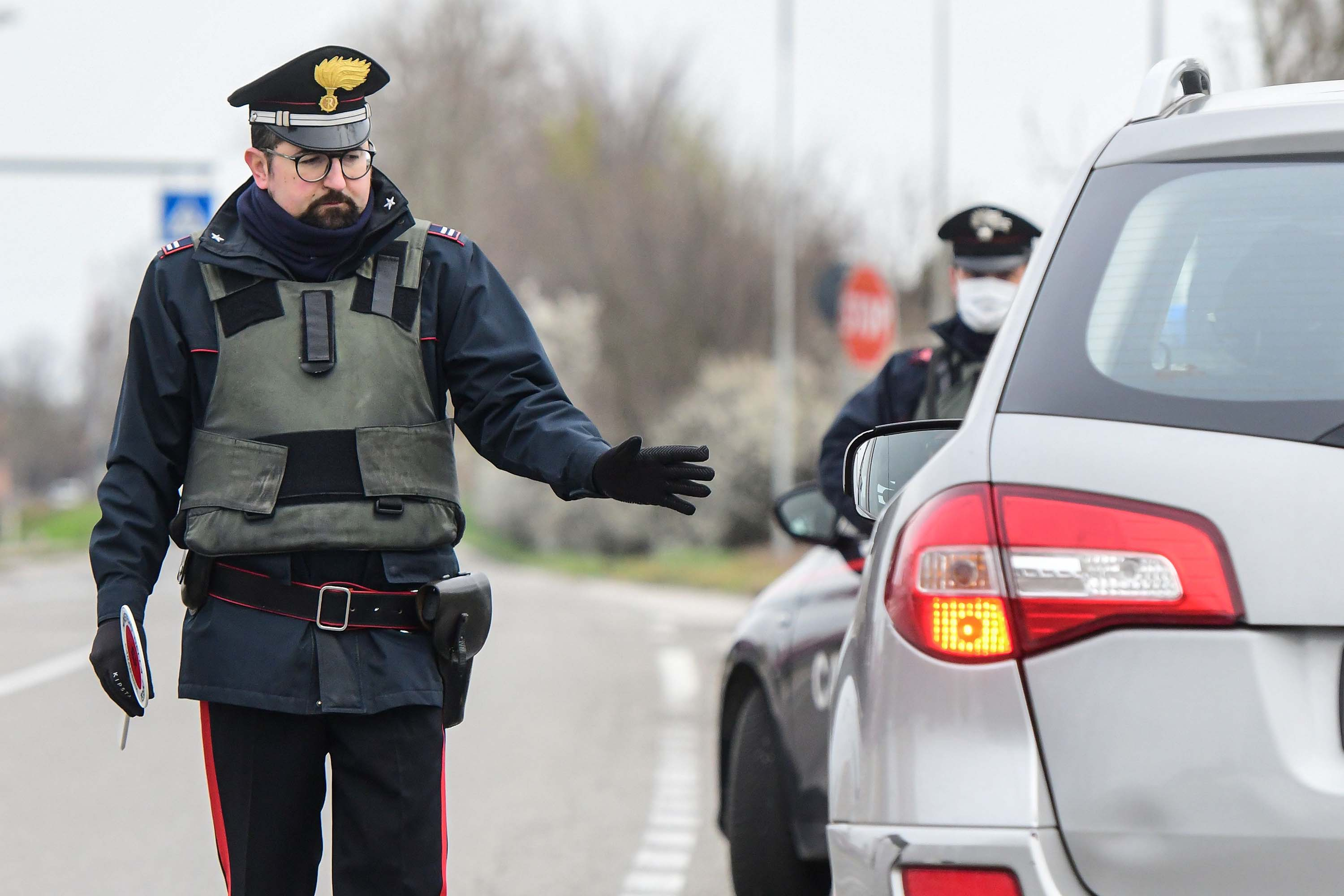 Italian Carabinieri police officers stop cars at a check point on the border between the quarantined provinces of Modena and Bologna in Valsamoggia, Italy, on Monday.