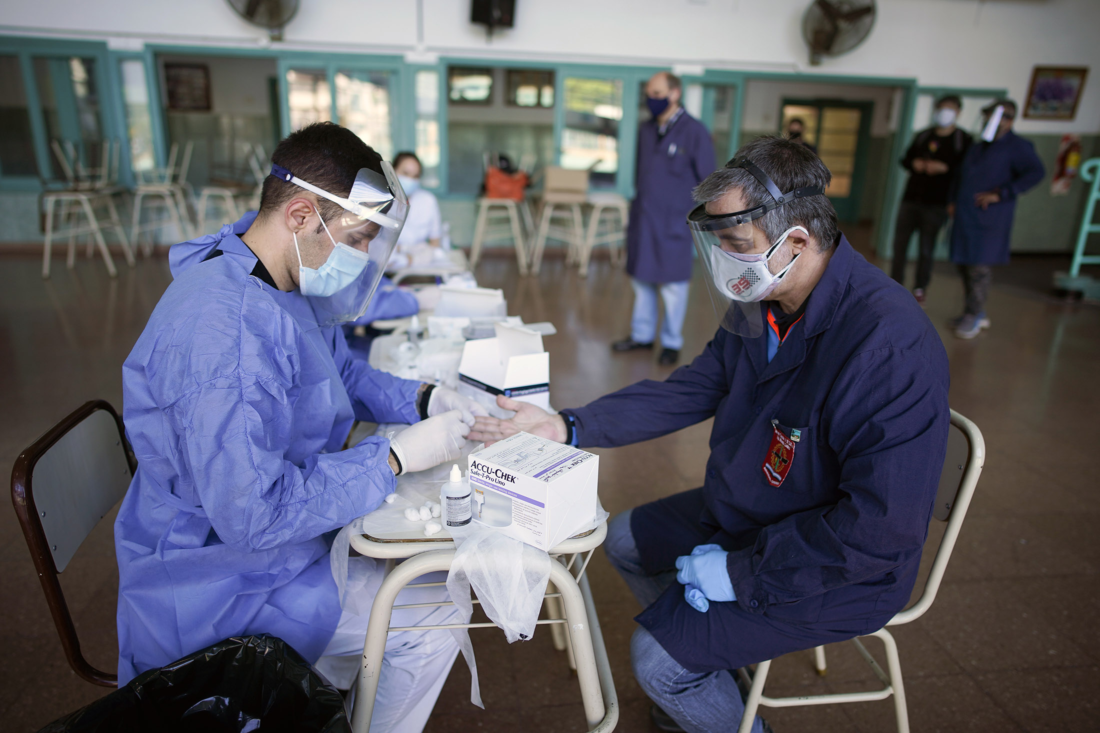 A health worker tests a teacher for COVID-19 in Buenos Aires, Argentina, on Tuesday, October 13.