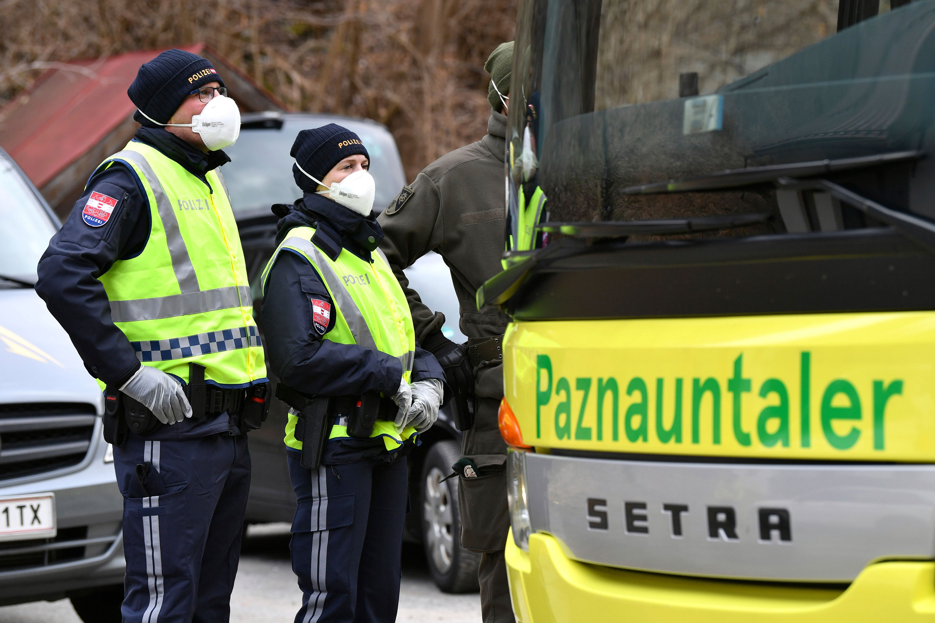 Police at a roadblock stop a bus from driving out of Paznauntal, Austria, on March 14. The towns of St. Anton am Arlberg in the Paznauntal area are isolated for 14 days.