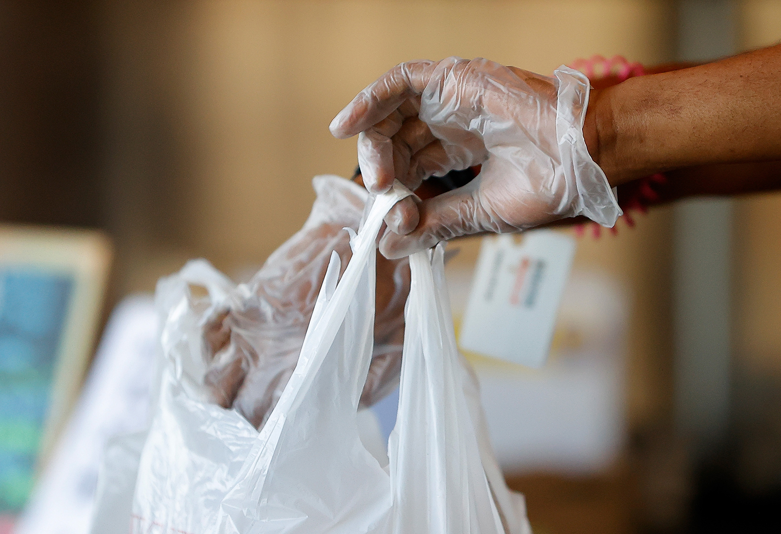 An employee is seen bringing to-go orders to the bar while wearing disposable gloves in Bad Daddy's Burger Bar as it reopened for dine-in seating on April 27, in Decatur, Georgia.
