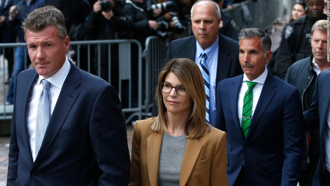 Actress Lori Loughlin, in tan at center, leaves as her husband Mossimo Giannulli, in green tie at right, follows behind her outside the John Joseph Moakley United States Courthouse in Boston on April 3, 2019.