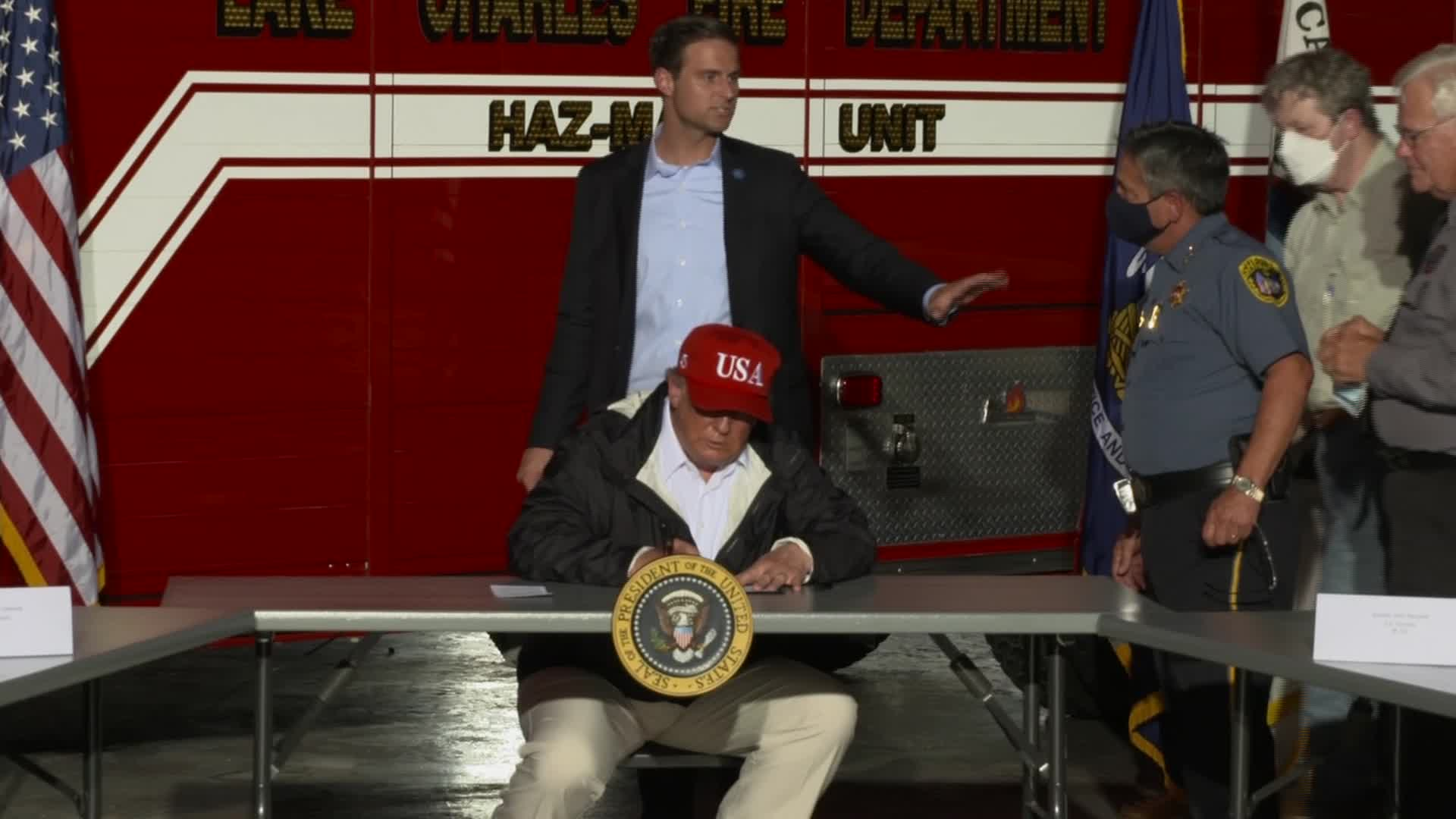 President Donald Trump's staff attempt to keep roundtable participants at a distance as a precaution at the end of a briefing on Hurricane Laura in Lake Charles, Louisiana, on Saturday, August 29.