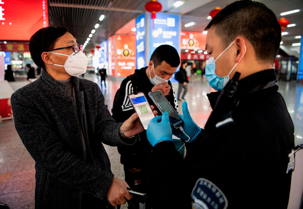 A passenger shows a green QR code on his phone to a security guard to indicate his health status at Wenzhou railway station in China on February 28.
