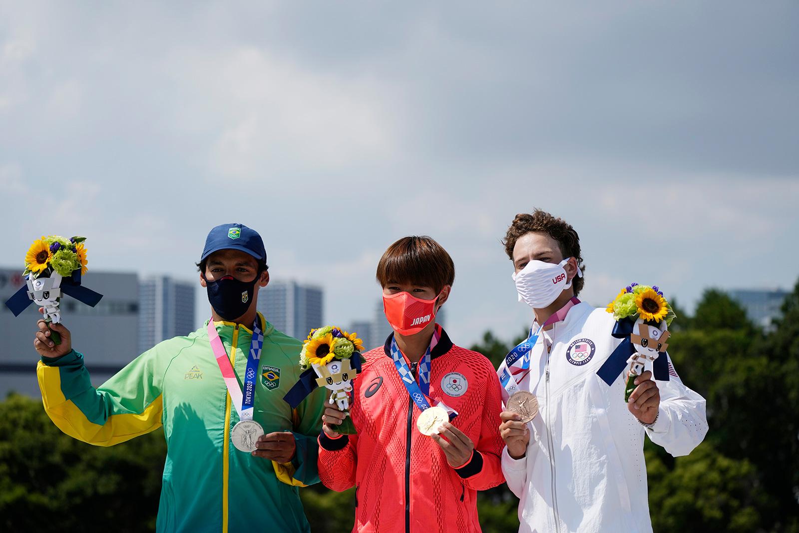 Kelvin Hoefler of Brazil, Yuto Horigome of Japan and Jagger Eton pose after the medal presentation at the men's street skateboarding finals on Sunday, July 25.