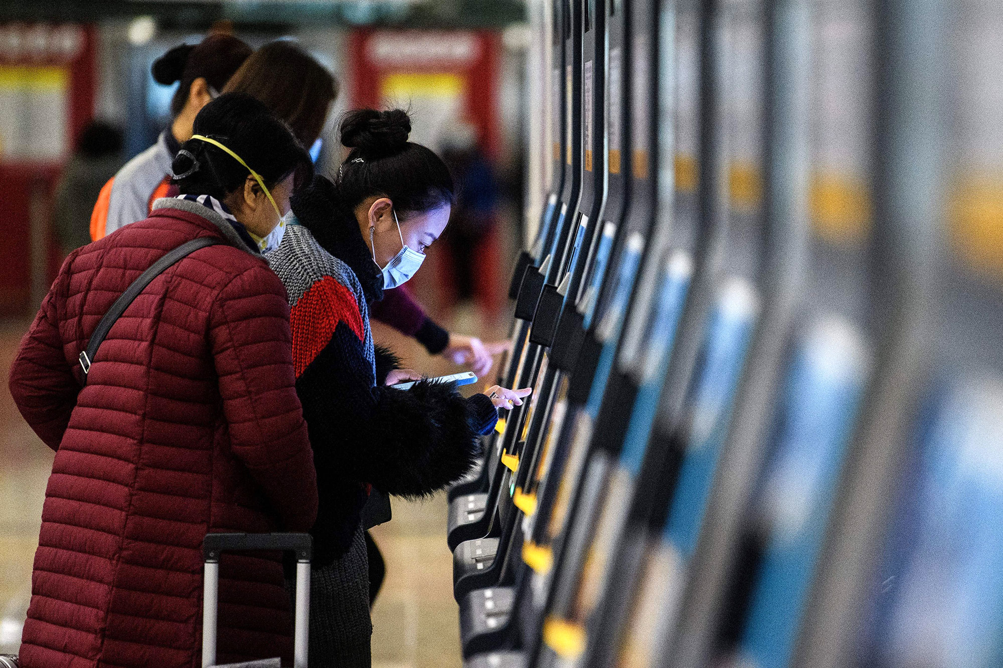 Commuters wear facemasks as they buy tickets inside the high-speed train station connecting Hong Kong to mainland China.