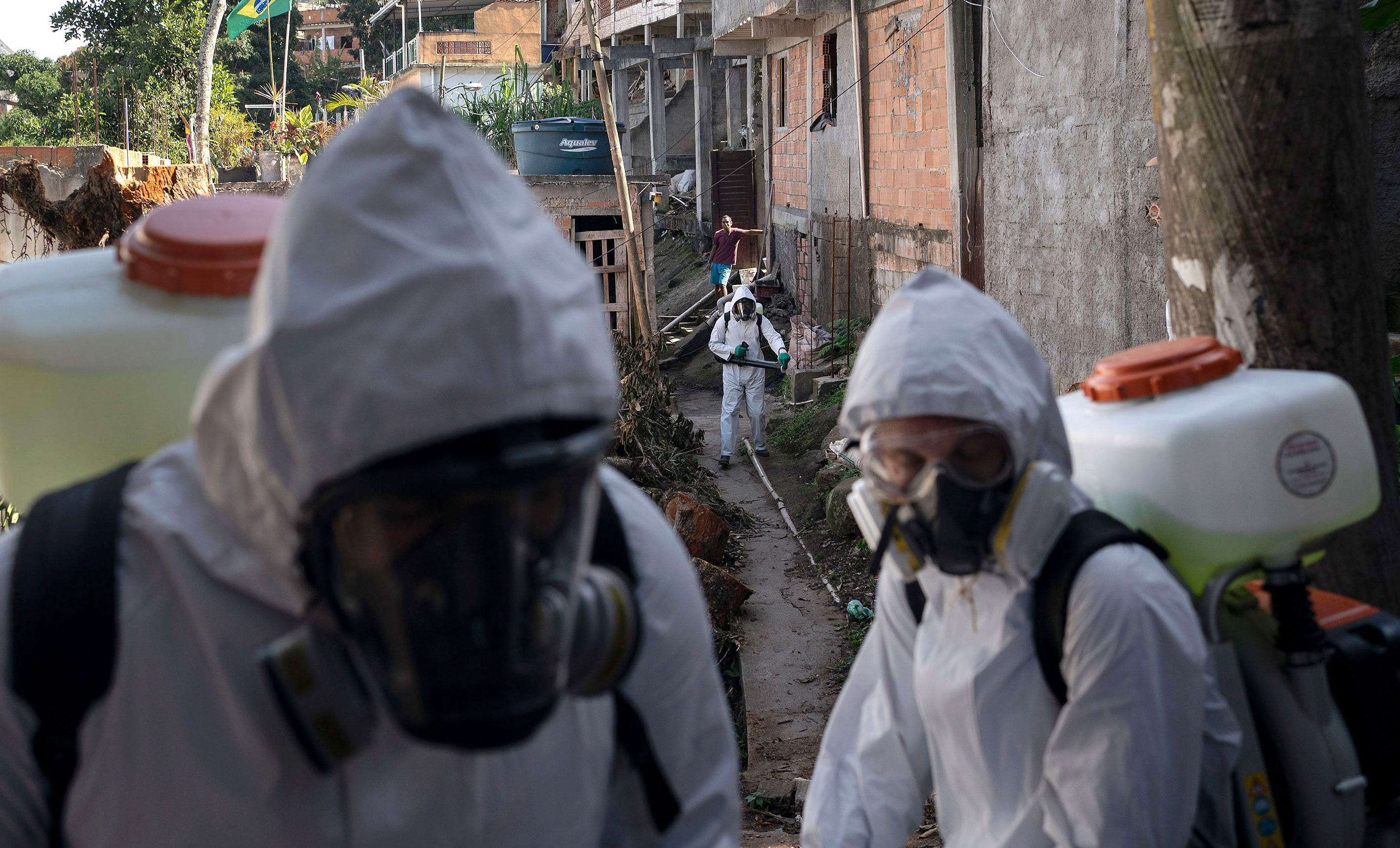 Volunteers spray disinfectant in an alleyway as a precaution against coronavirus on July 12 in Rio de Janeiro, Brazil.