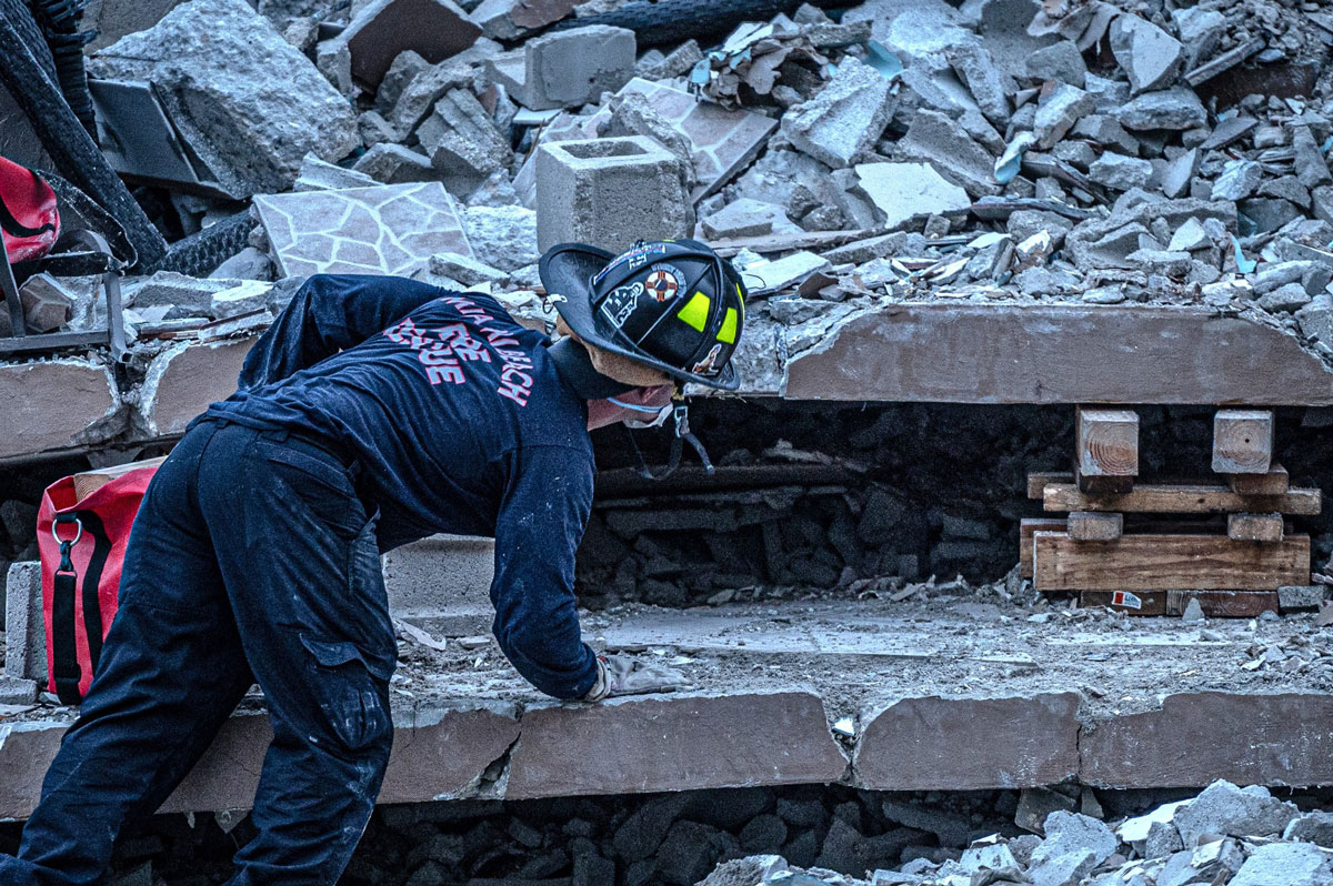 Members of the South Florida Urban Search and Rescue team work in the rubble of the partially collapsed 12-story condo building.