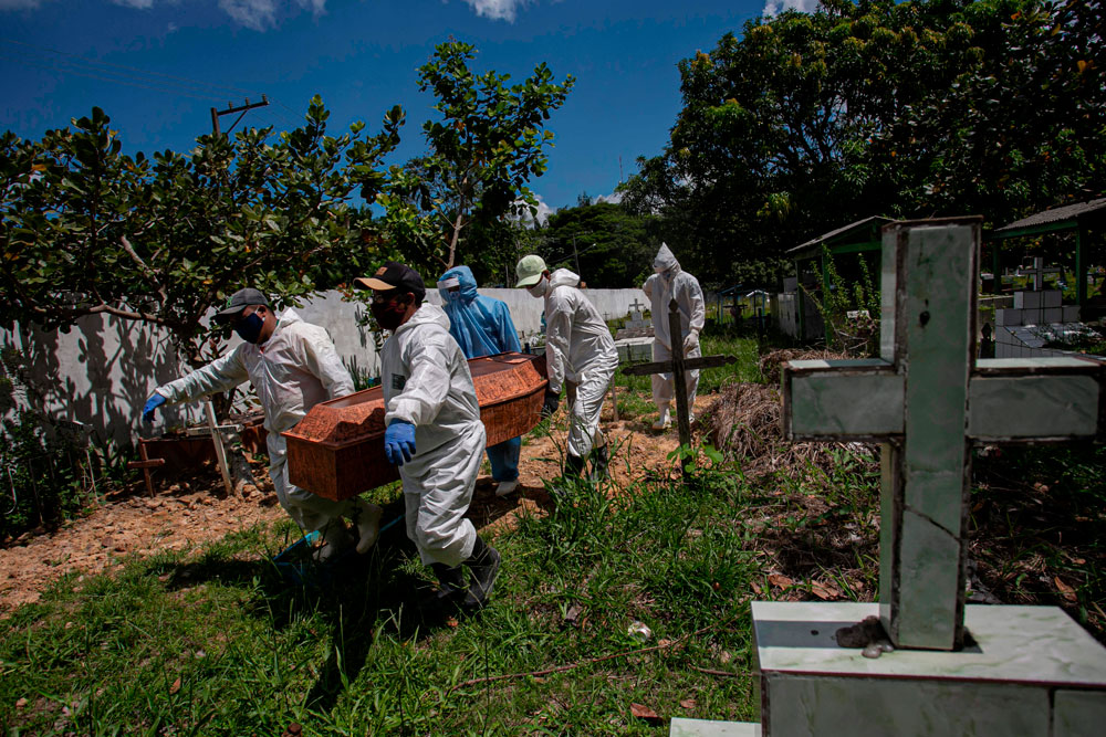Cemetery workers carry a coffin at the municipal cemetery Recanto da Paz in Breves, Brazil, on June 7.