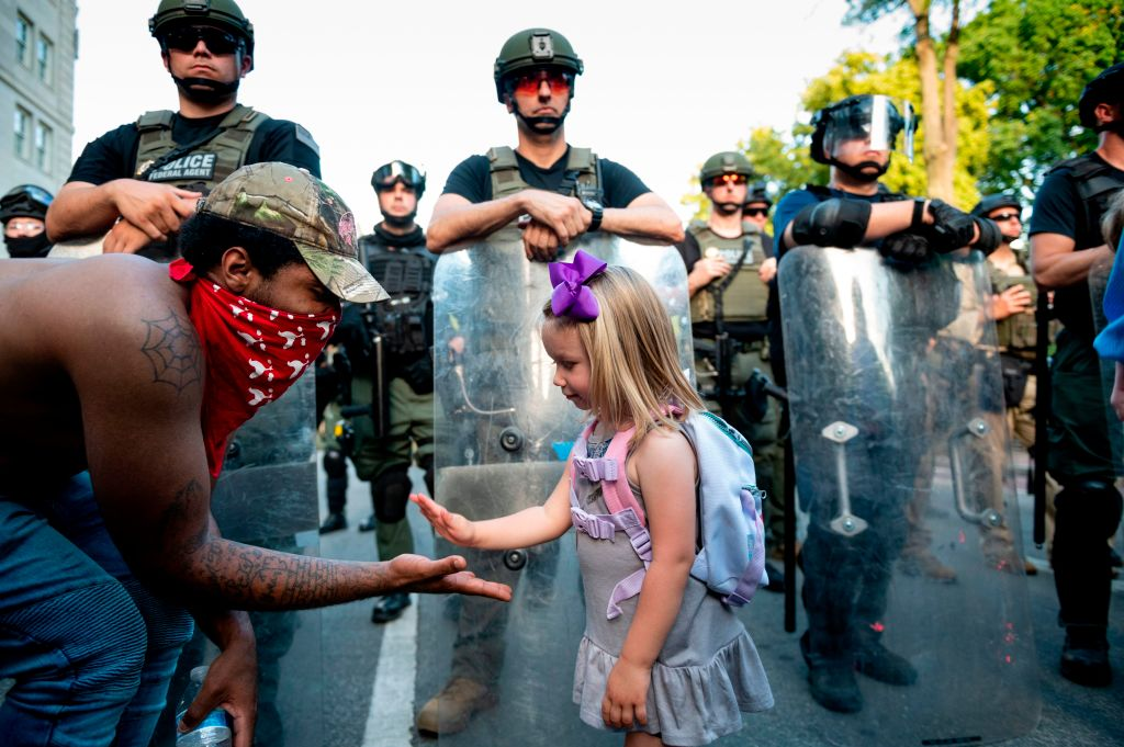 Twenty-nine-year old DC resident, George (L), slaps hands with three-year-old Mikaela (R) in front of a police barricade on a street leading to the front of the White House during protests on June 3.
