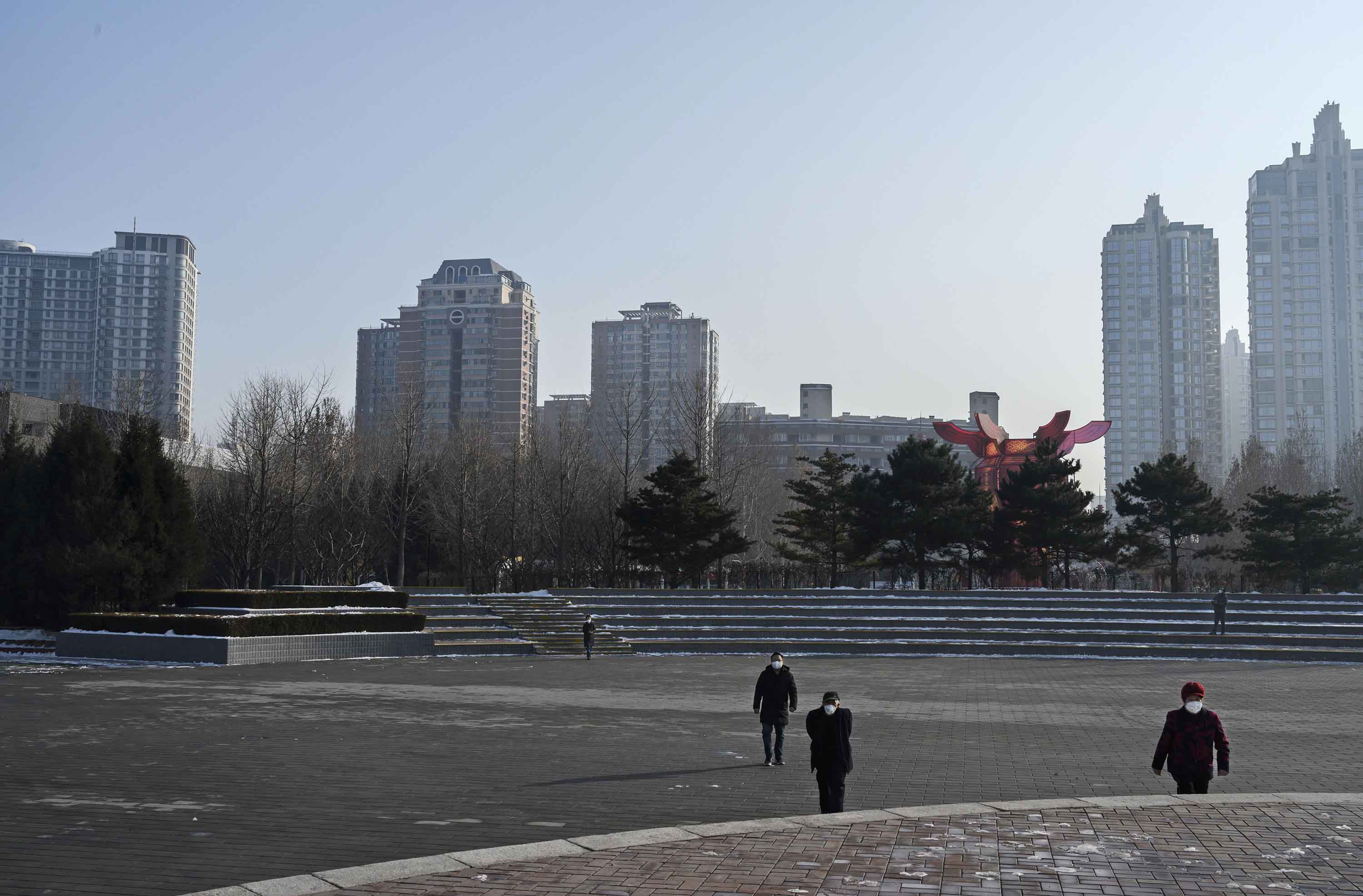 People wear protective masks as they walk in a nearly empty Chaoyang Park in Beijing on Sunday.