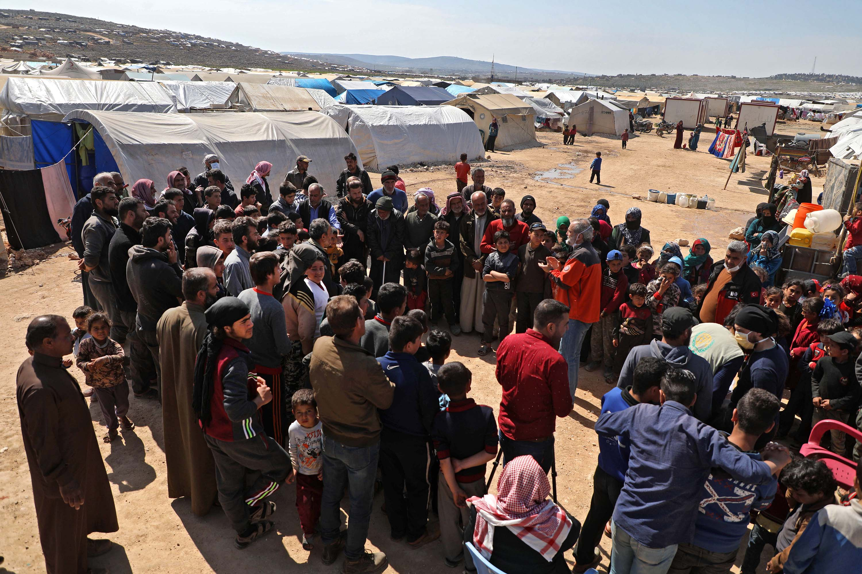 Medical staff from a Turkish humanitarian group give a lecture to raise awareness about the coronavirus epidemic at a camp for displaced Syrians in Kafr Lusin, on the border with Turkey, in Syria's northwestern province of Idlib, on March 23.