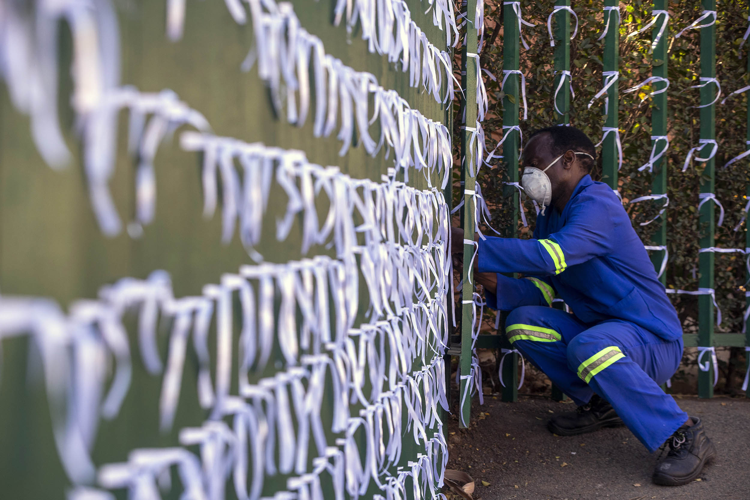 A caretaker ties ribbons onto a fence to represent South Africans who died from Covid-19, at St James Presbyterian church in Johannesburg, South Africa, on Wednesday, July 29.
