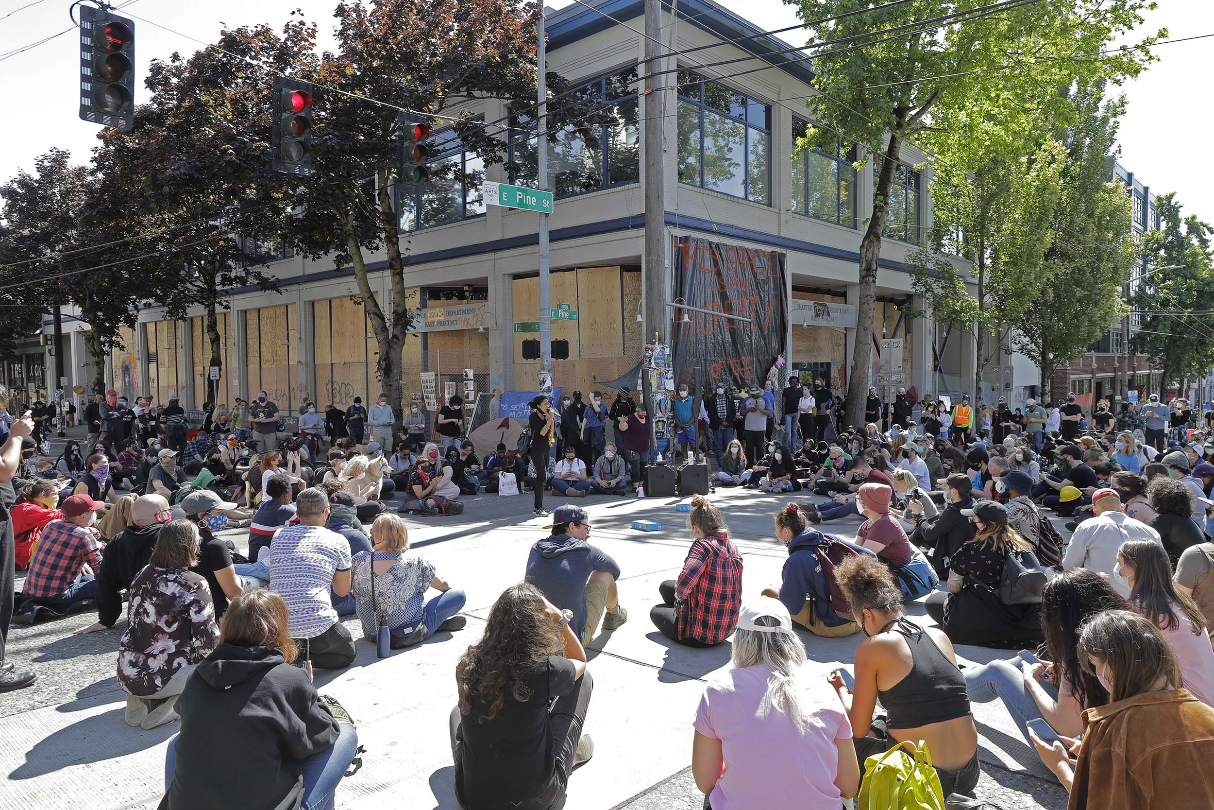 Protesters listen to a speaker as they sit in front of the Seattle Police Department East Precinct building, on Thursday, June 11.