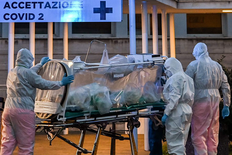 A patient in a biocontainment unit is carried on a stretcher at the Columbus Covid 2 Hospital in Rome, Monday, March 16.