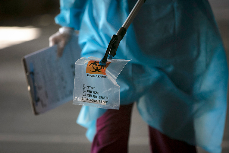 A physician assistant carries a nasal swab sample using a grabber at a drive-through testing site set up at the Anaheim Convention Center in Anaheim, California, on Thursday, July 16.