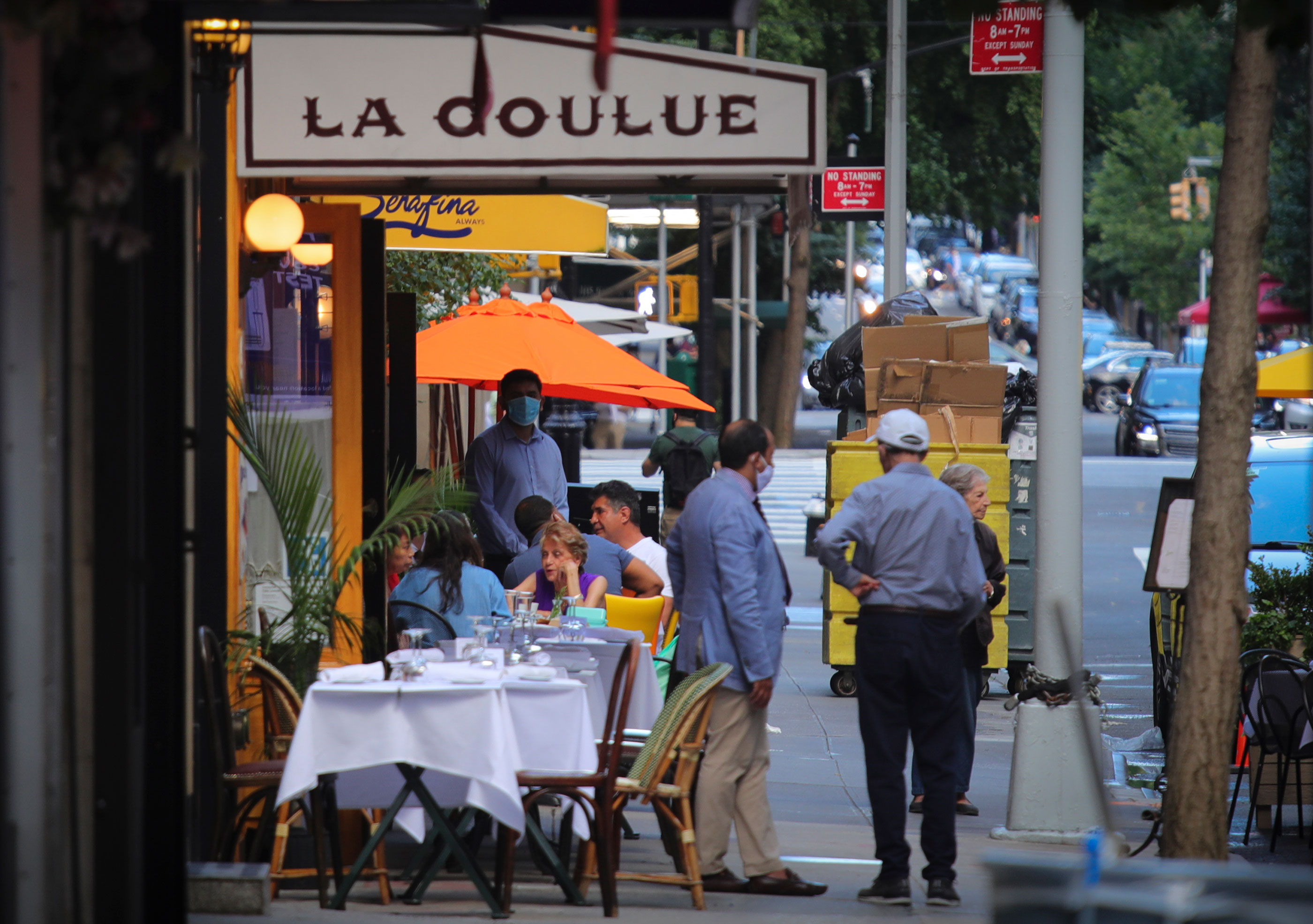 Diners eat outside of a restaurant on July 1 in New York.