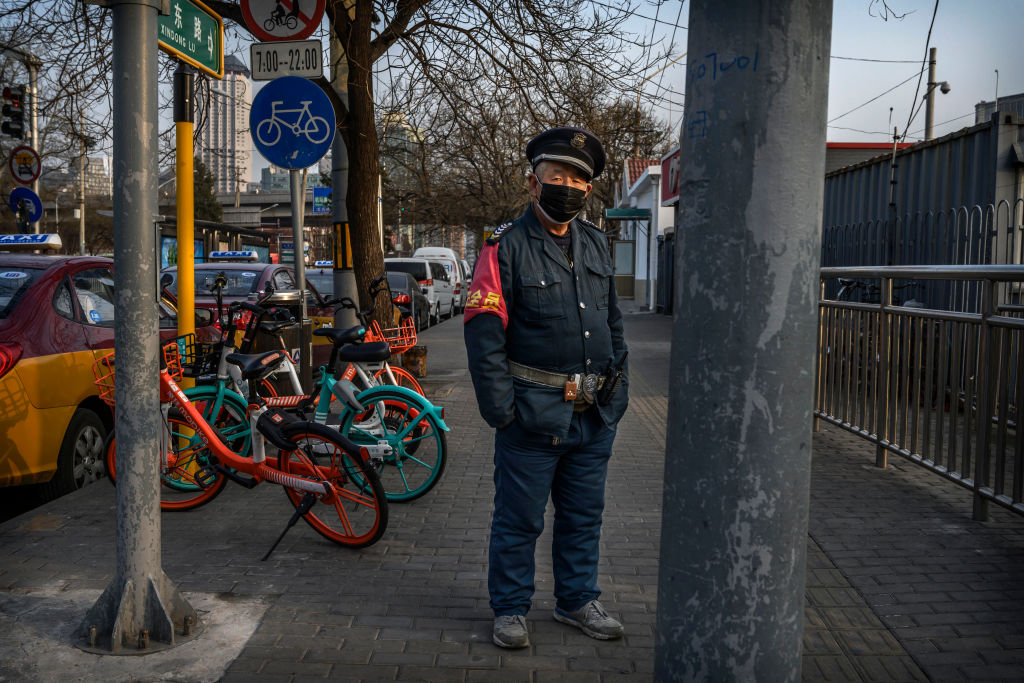 A Chinese transit worker wears a protective mask as he waits at a bus station on February 25, 2020 in Beijing, China.