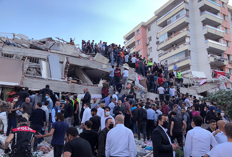 Rescue workers and local residents try to reach people trapped in the debris of a collapsed building in Izmir, Turkey, Friday, Oct. 30, 2020.