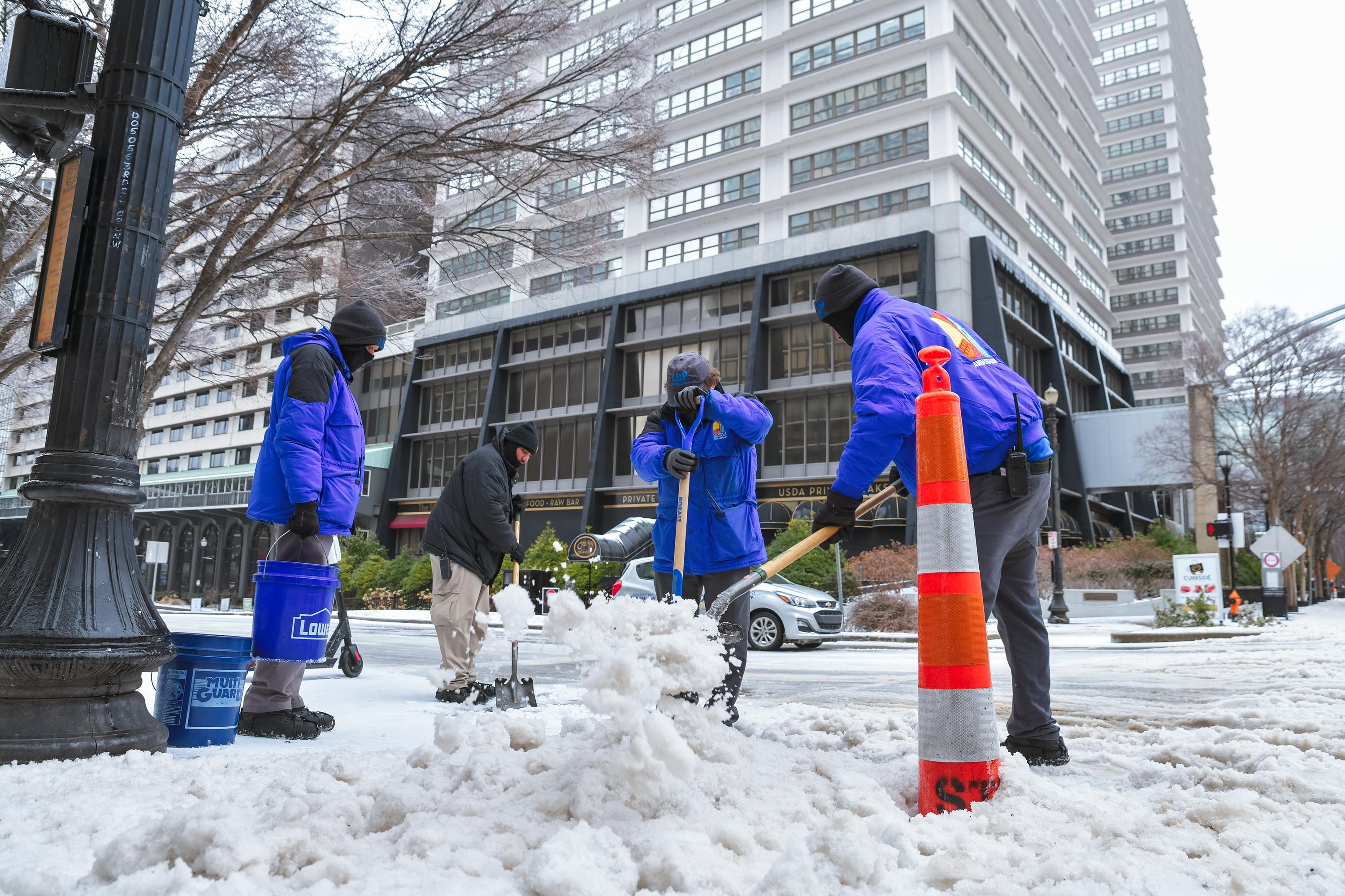City workers use shovels to chip away at ice on the sidewalk in downtown Louisville on February 11, 2021 in Louisville, Kentucky.