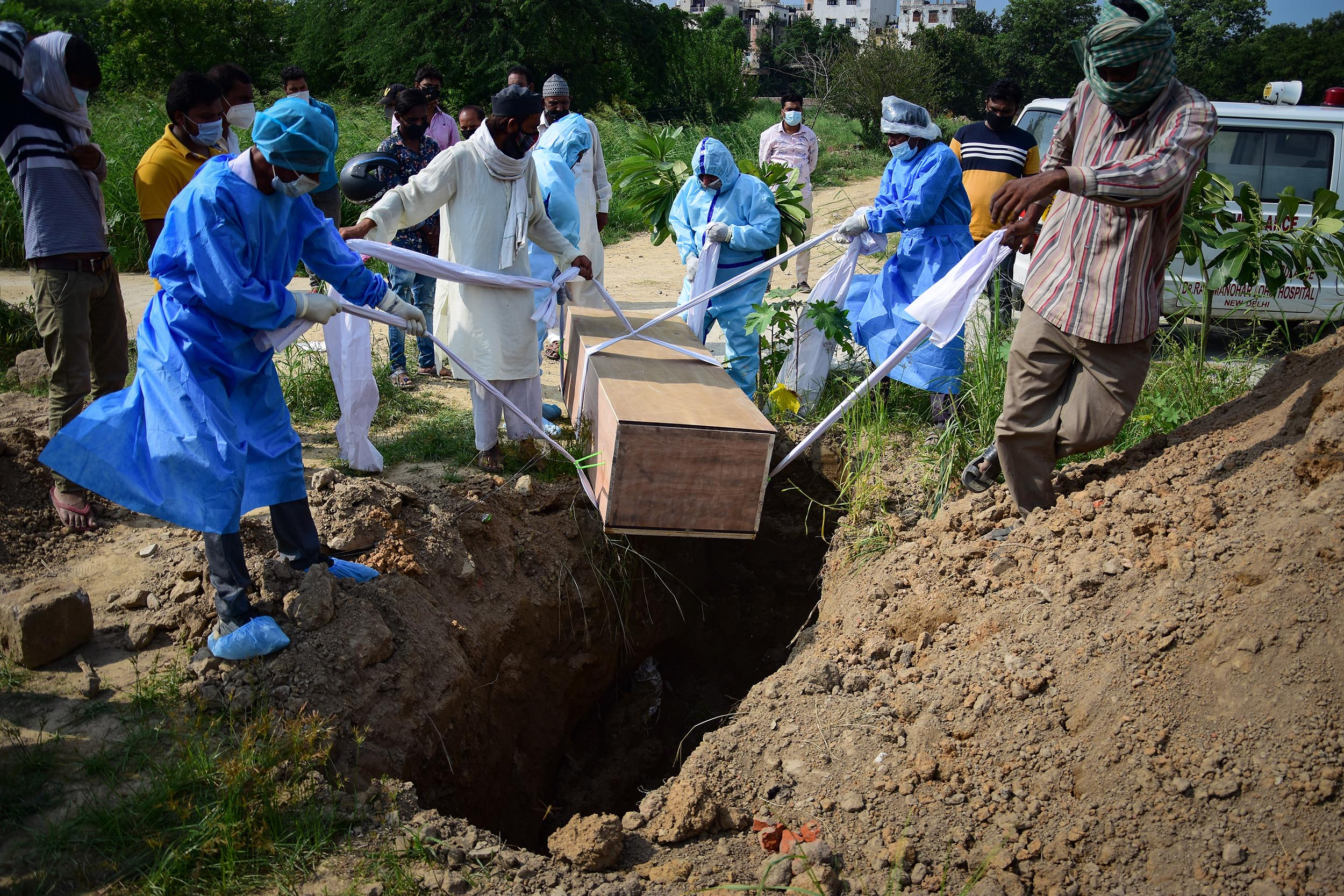 Relatives wearing personal protective equipment (PPE) as a precaution lower the body of a COVID-19 victim for burial at a graveyard in New Delhi, India.