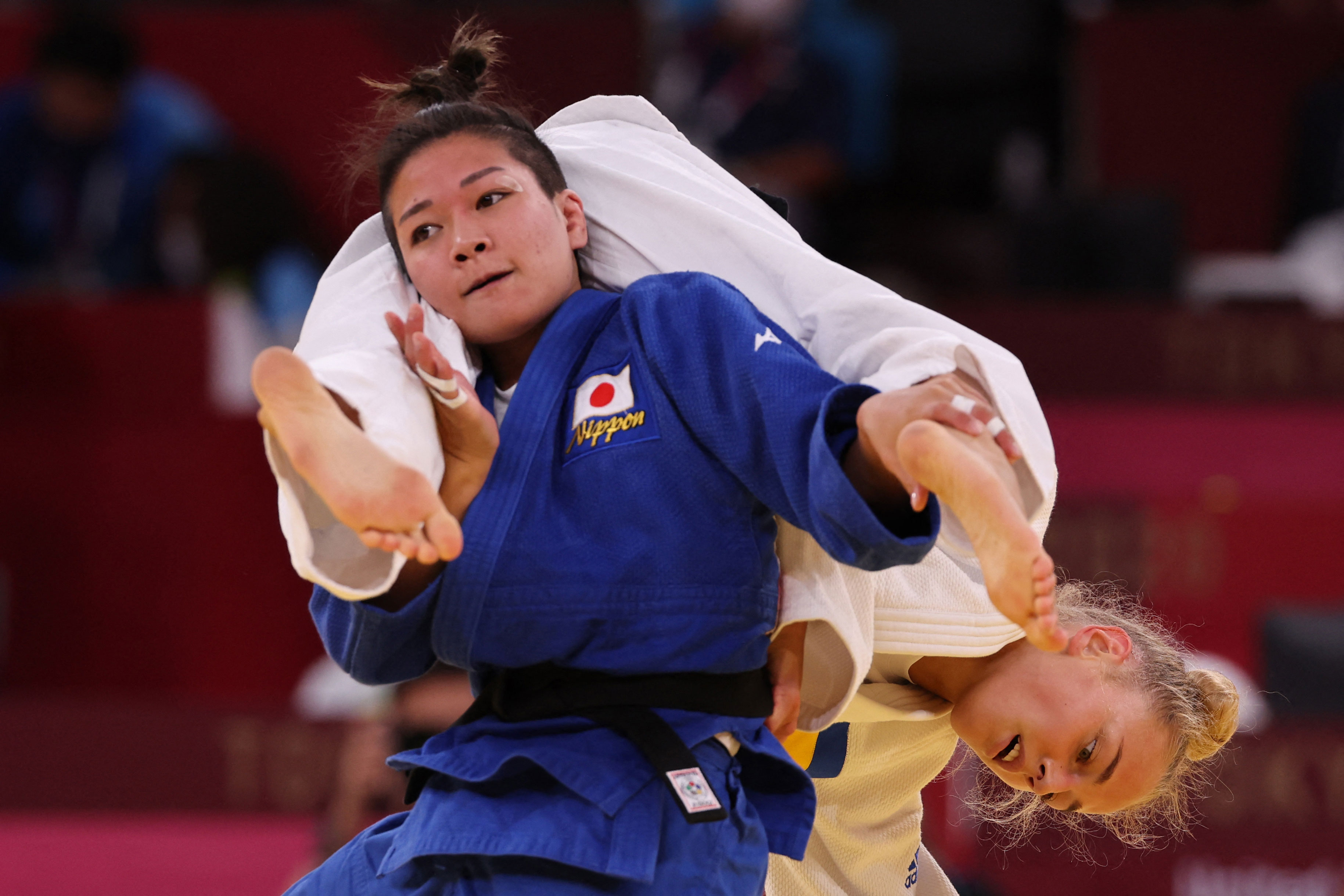 Japan's Funa Tonaki, in blue, competes with Ukraine's Daria Bilodid during their judo women's -48kg semifinal B bout on July 24.