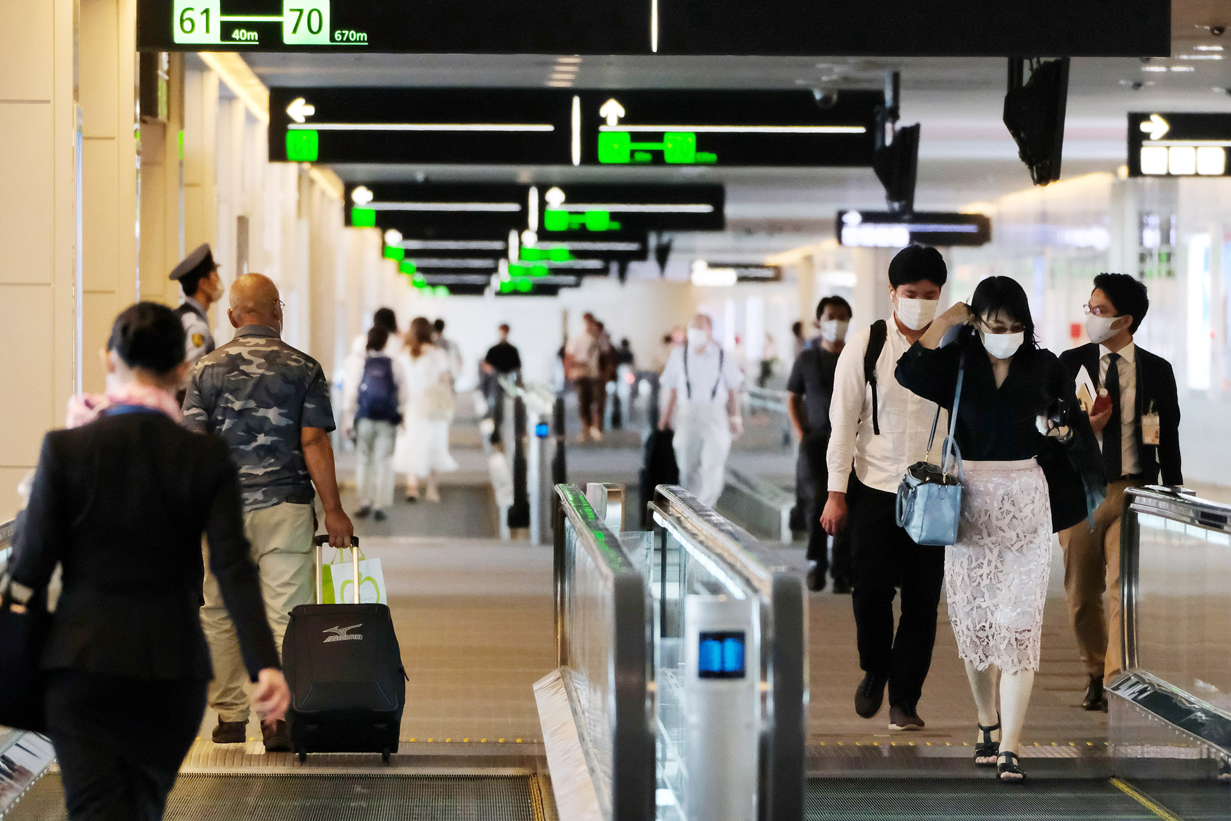 Passengers head to their departure gates at the domestic terminal of Tokyo's Haneda airport in Japan, on July 25.